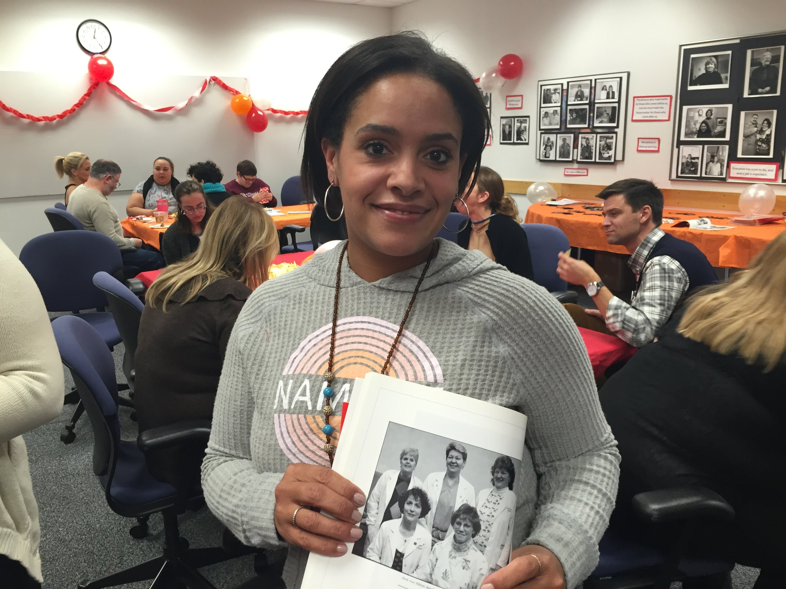 Current SHARE member Dinea Williams, holding a SHARE yearbook photo of her mother, Dianne Williams, who voted in our union twenty years ago