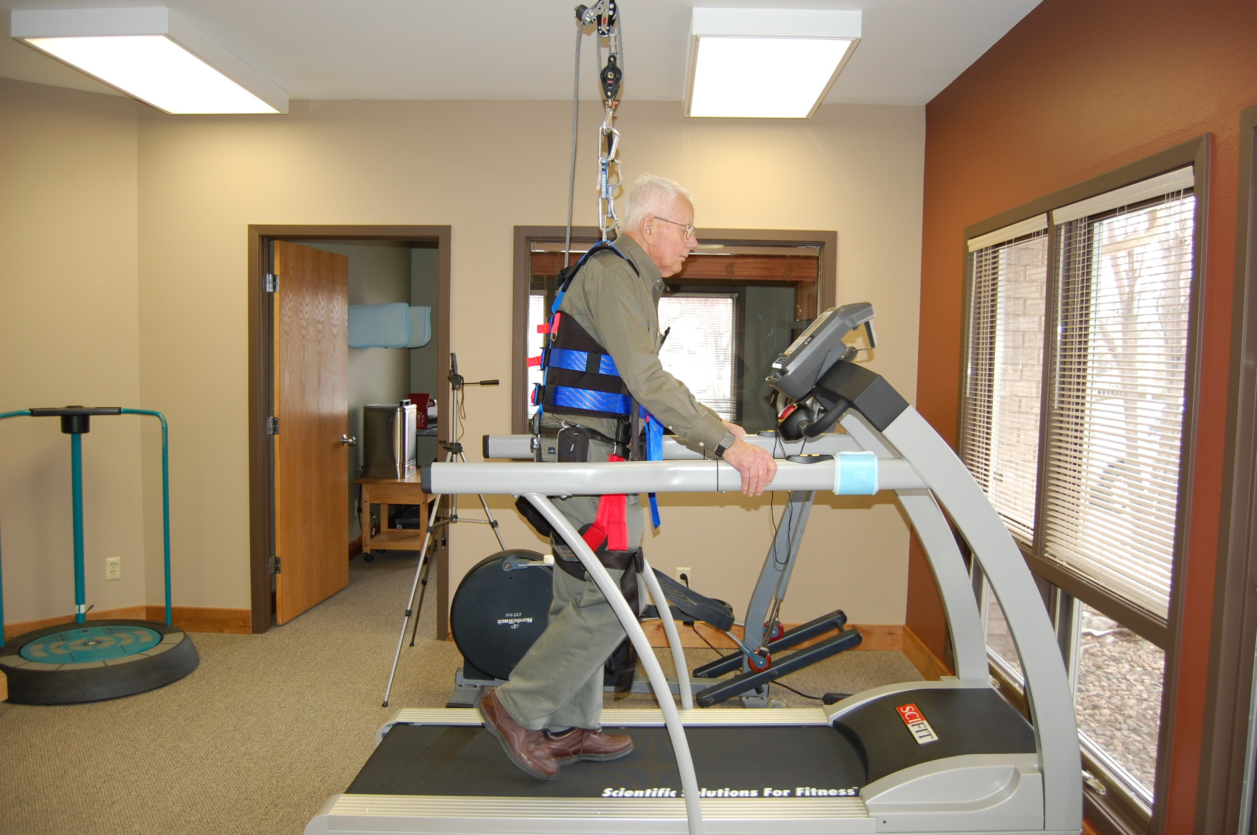 Individual using the body weight support harness on the treadmill to enhance his ability to walk.