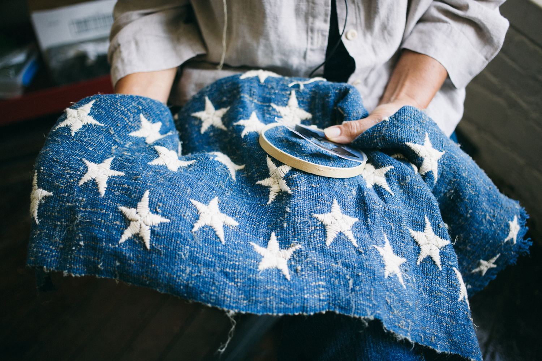 Harvesting_Liberty_Donnie Hedden-23 Debra Kriekel hand embroidering the stars on the American flag.jpg