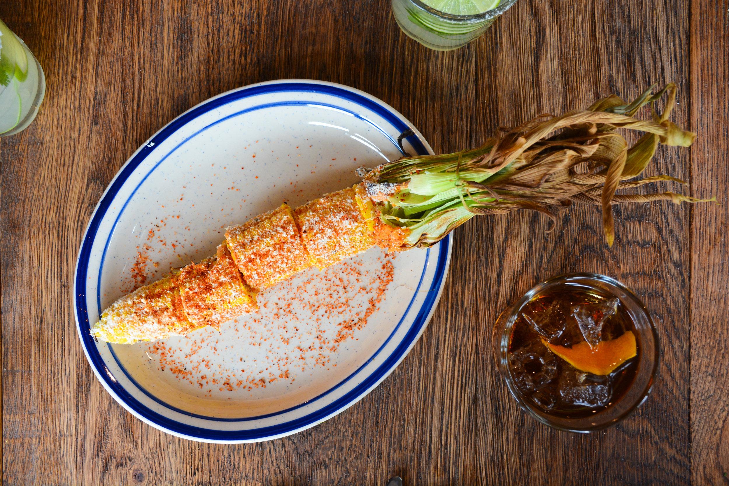 Elote Loco from La Puerta Verde - corn on the cob with spicy citrus mayo, chili &cojita cheese