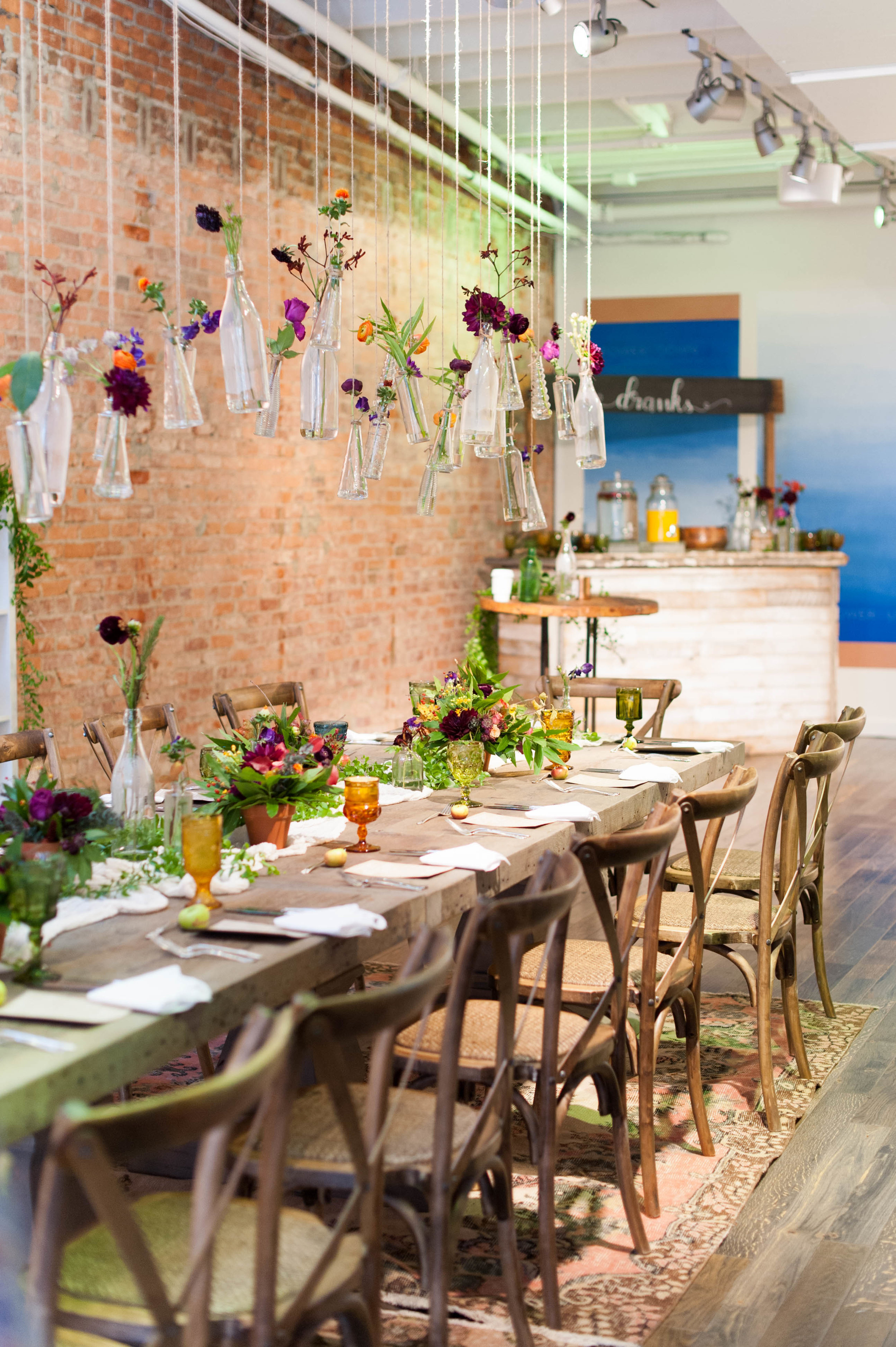 Overall catering, styling and design by  HeirloomDC  @heirloomdc -- love the hanging glass bottles with flowers as a chandelier centerpiece.