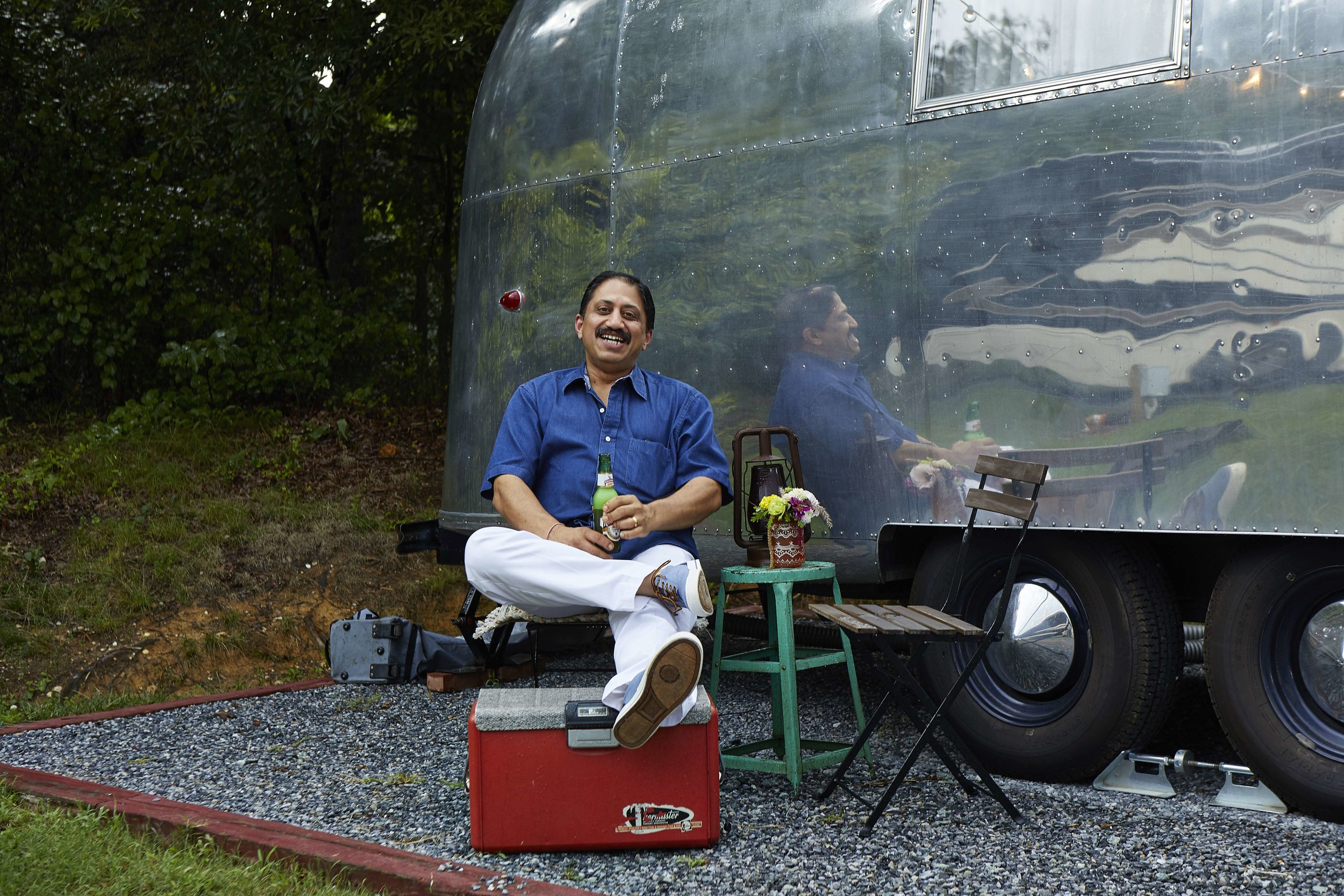 Chef Vikram Sunderam relaxes in front of a vintage Airstream at a family cookout.