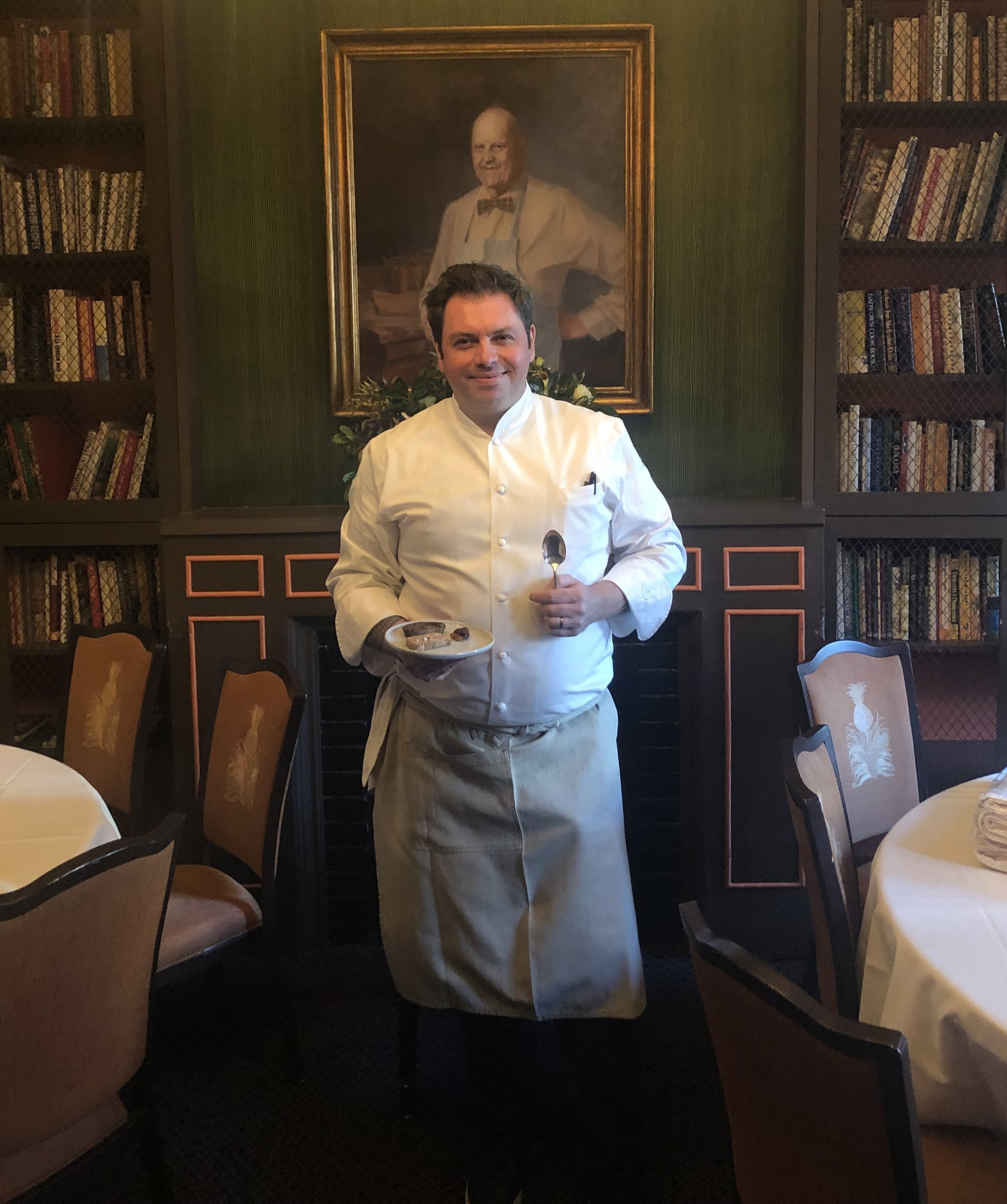 Chef Sebastien Rondier of Brabo stands in front of a portrait of James Beard at the James Beard House in NYC.