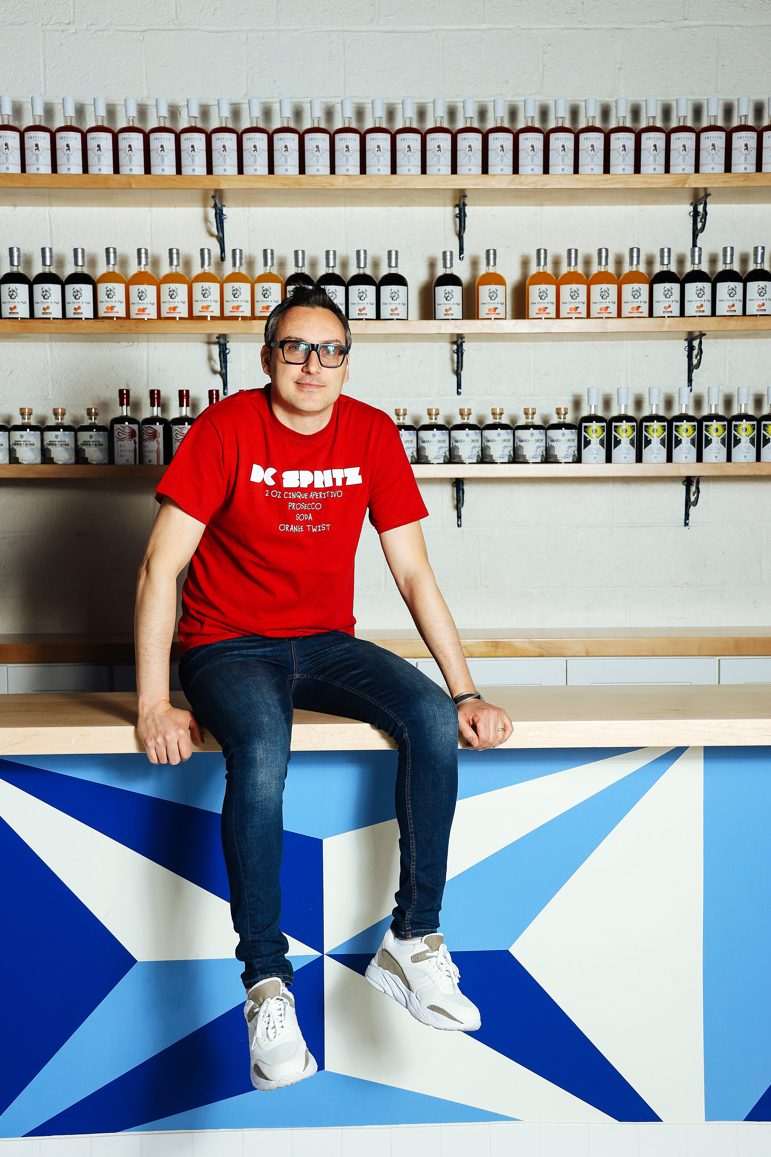 Amodeo on his tasting bar, his locally produced product behind him.