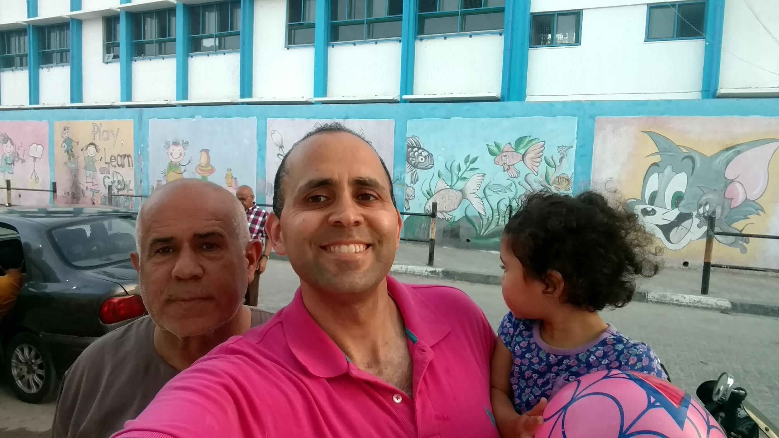 Hani and his uncle and daughter in front of an UNRWA school in the Gaza Strip