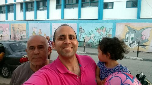 Image: Hani and his uncle and daughter in front of an UNRWA school in the Gaza Strip