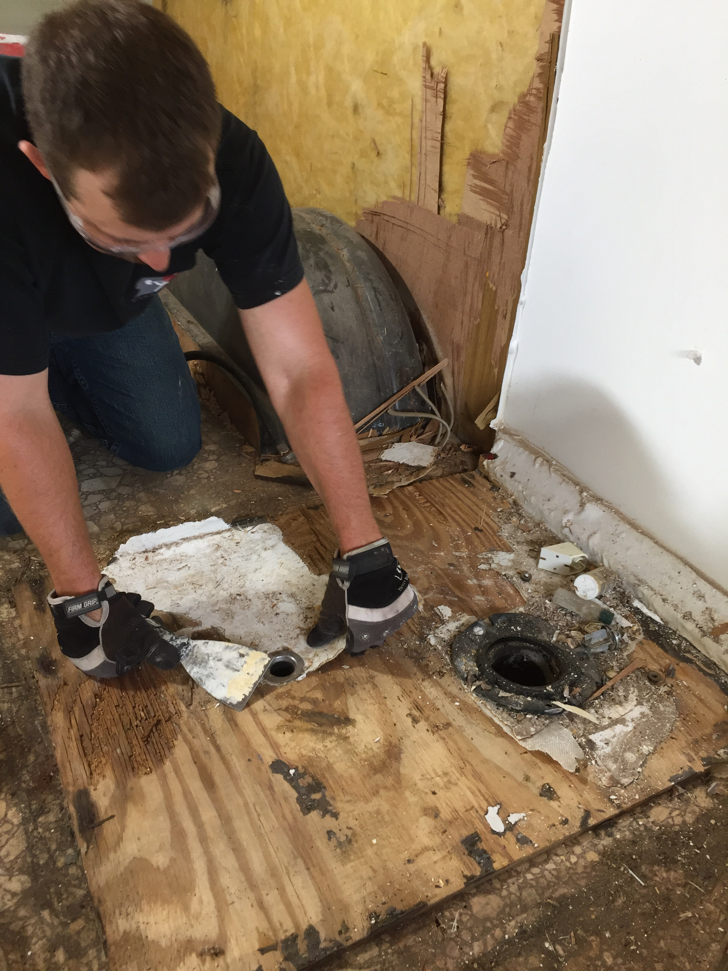 Scraping and chipping off the waterproof, fiberglass coating bit by bit to uncover the screws and rotted shower floor.
