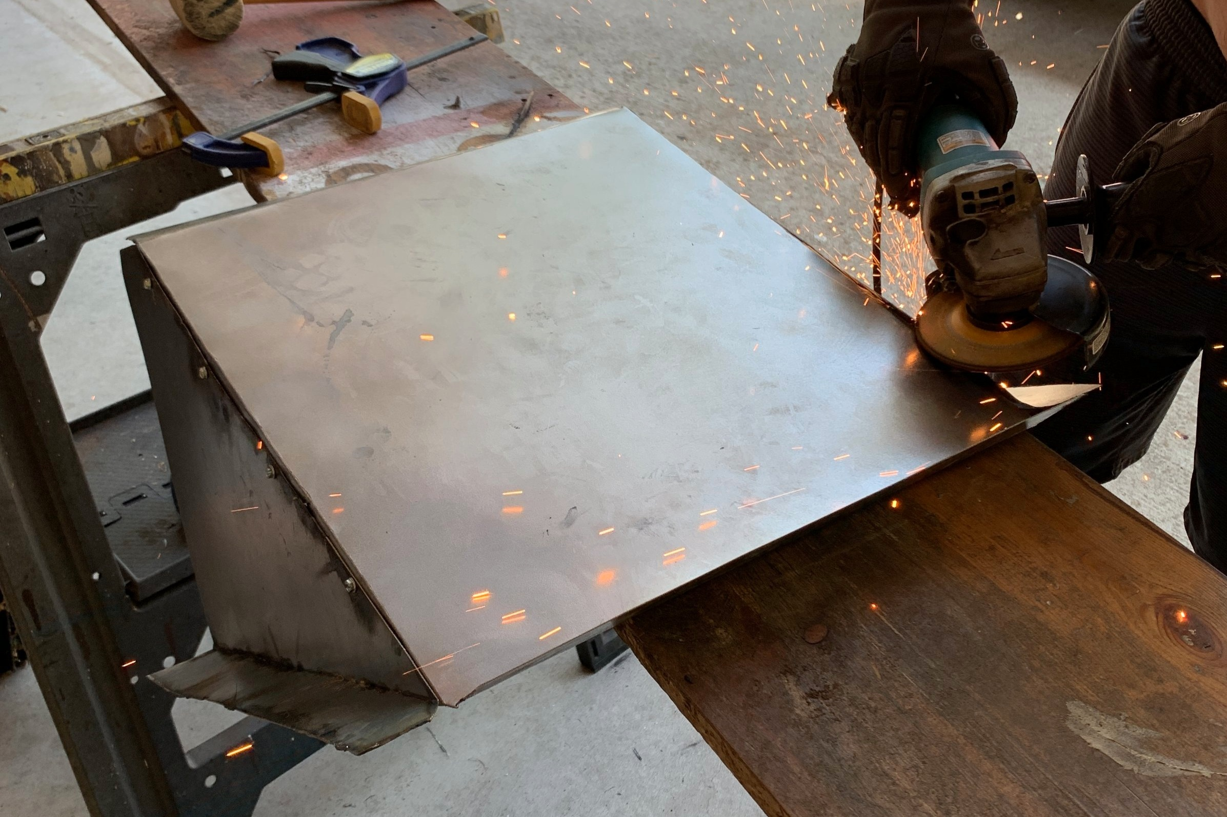 Grinding off the excess metal to smooth the edge of our duct.