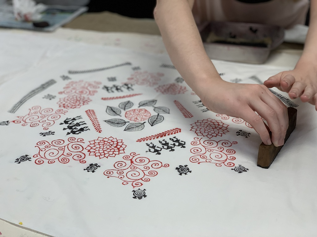 Detail shot of a student creating a handkerchief design in Traditional Sanganeri Block Printing with Shanti Jain