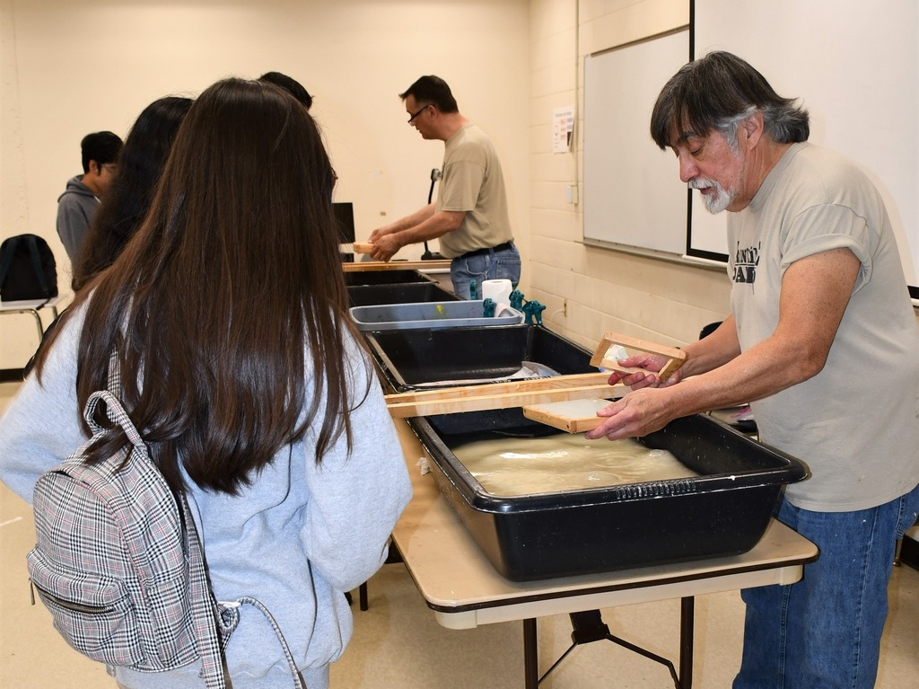 Walt Nygard and Ron Erickson work with students to make paper.