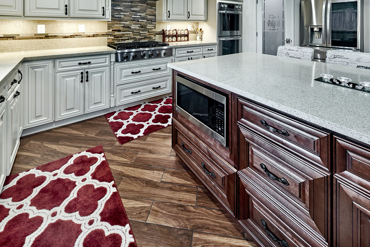 TWO TONE KITCHEN CABINETS WITH UNDER COUNTER MICROWAVE IN ISLAND.