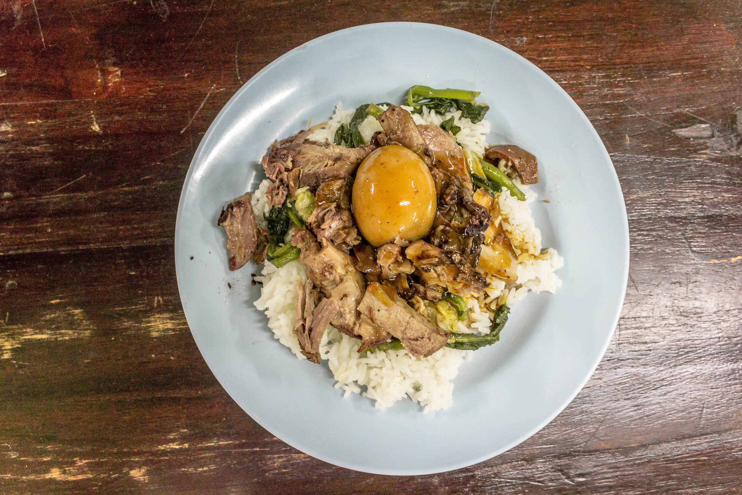 pork leg served with rice, morning glory, special sauce, and a hard-boiled egg