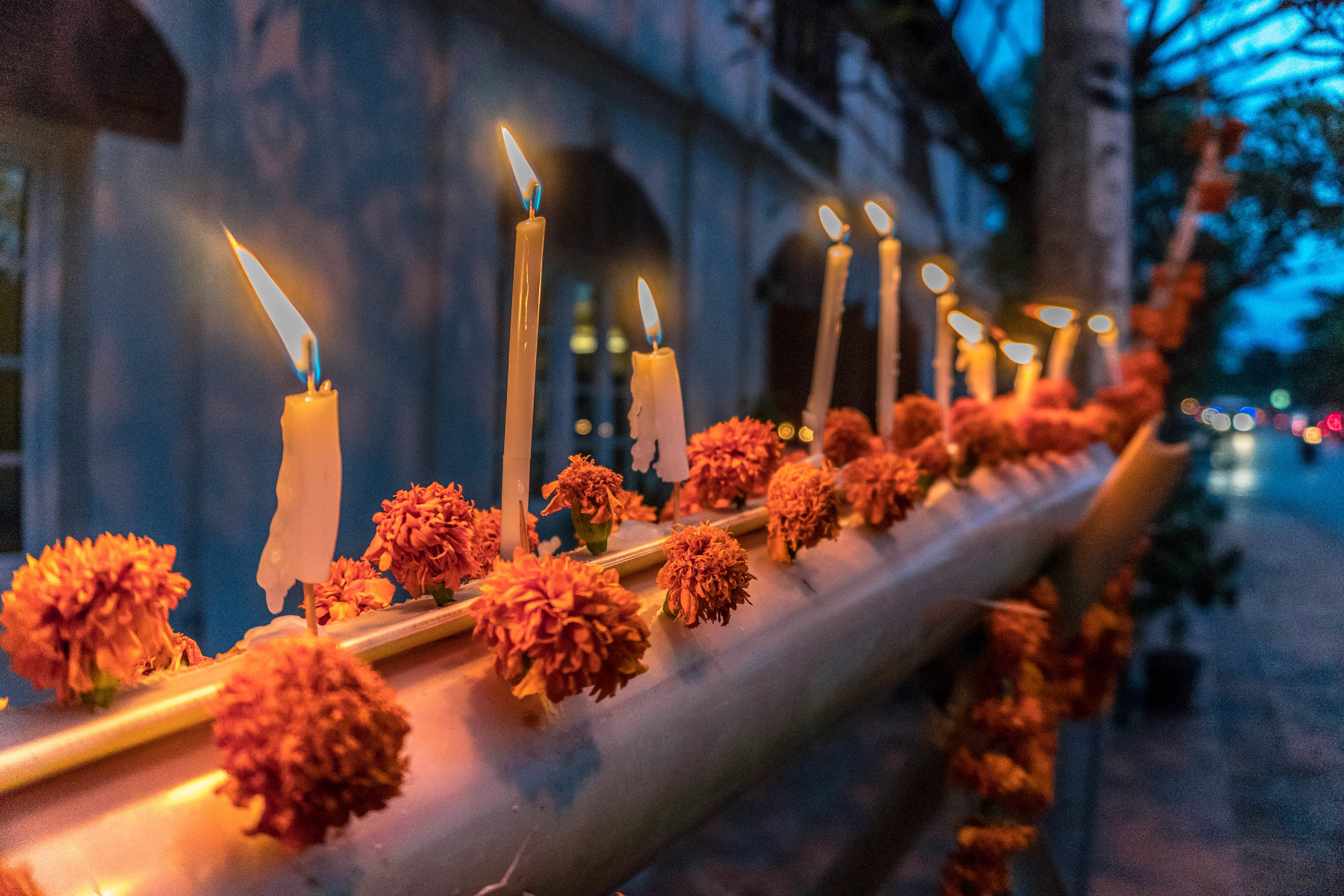 CANDLES BEING LIT AT DUSK
