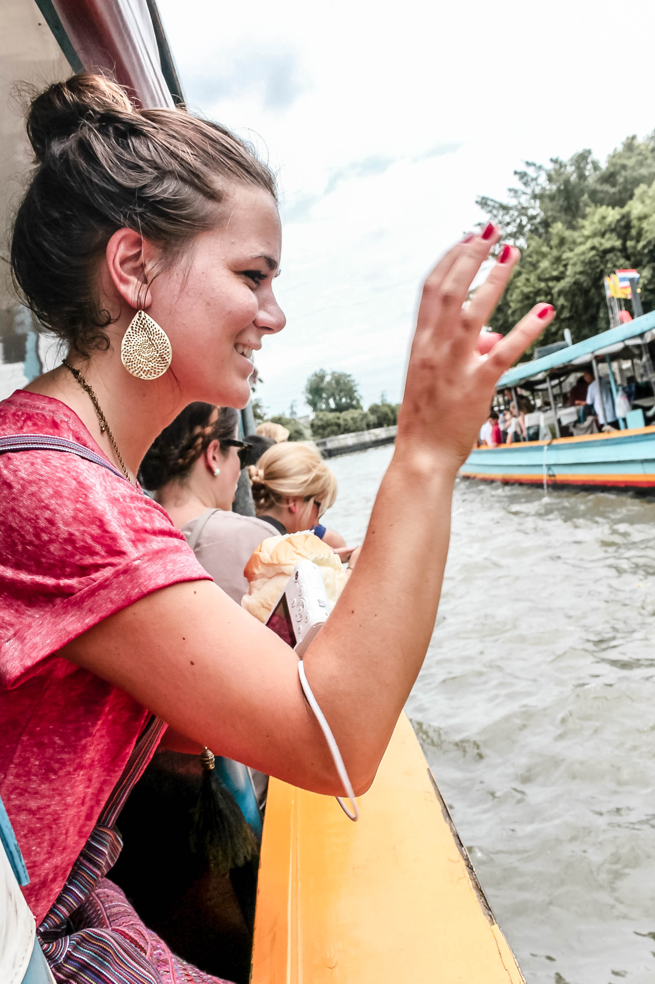 THIS QUEEN IN HER BIG EARRINGS FEEDING FISH CARELESSLY ON THE WATERWAYS OF BANGKOK IN 2013