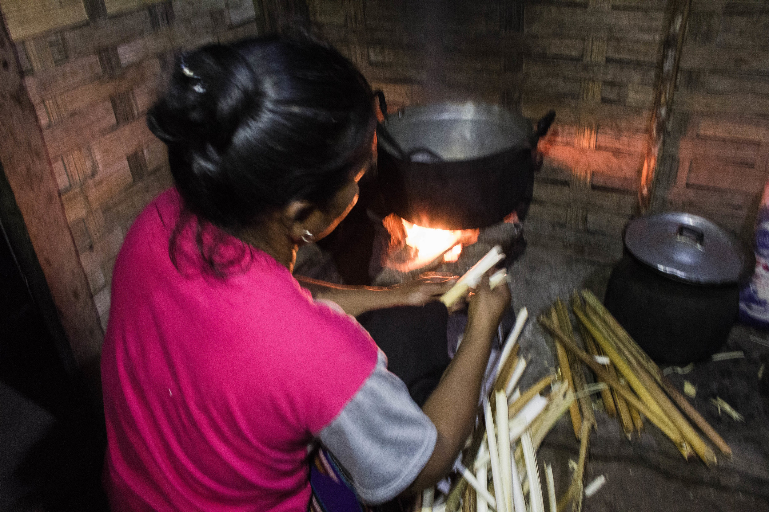 A WOMAN FROM NA LAN VILLAGE COOKS OUR DINNER OVER A FIRE WITH A SINGLE LIGHTBULB