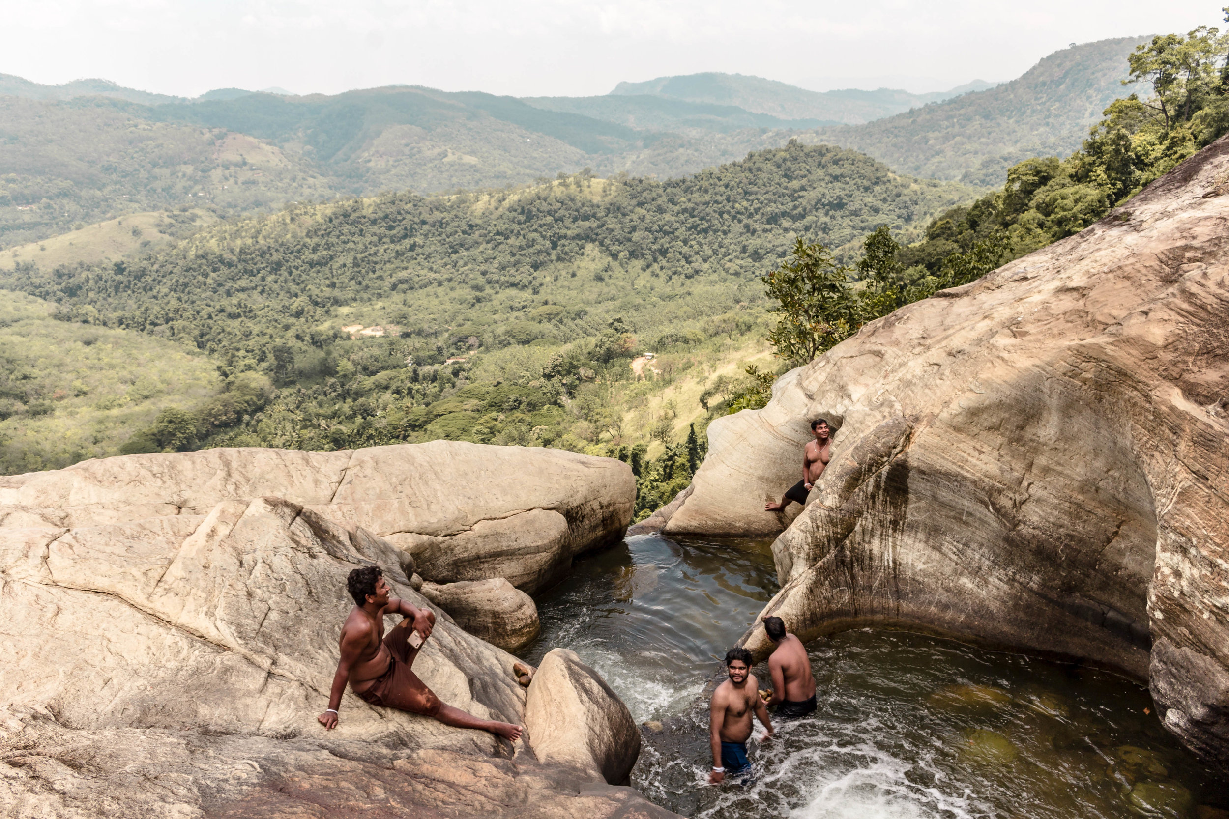 LOCAL MEN SWIMMING IN THE POOLS AT THE TOP OF THE LOWER FALLS