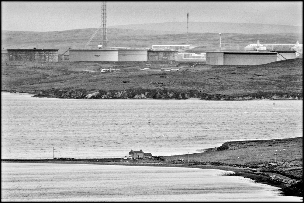 Lornies house is dwarfed by the tanks at Sullom Voe terminal