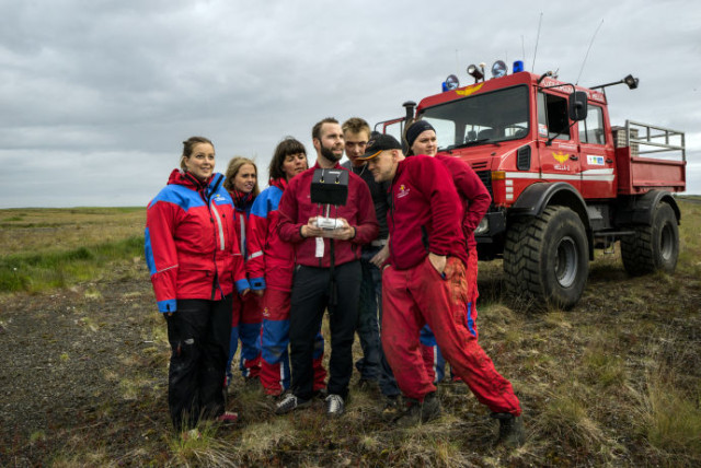 HELLA, ICELAND - JULY 6 2015: The members of the all-volunteer Hella mountain rescue team, know locally as Slysavarnarfélagið Landsbjörg or ICE-SAR, crowd around a thermal camera equipped drone controller during a practice search and rescue session on July 6, 2015 in the outskirts of Hella, Iceland. (Photo by Benjamin Lowy/Getty Images Reportage for The New Yorker Magazine)
