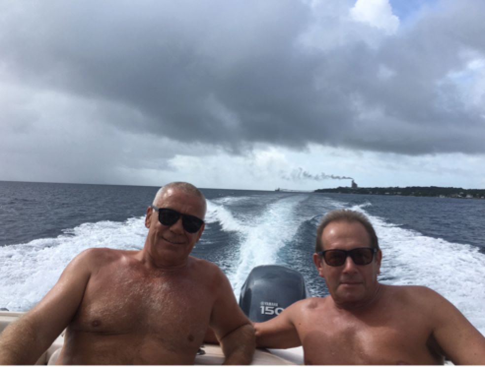 Charlie and Dom on the high seas with the environmentally friendly cement factory in the background