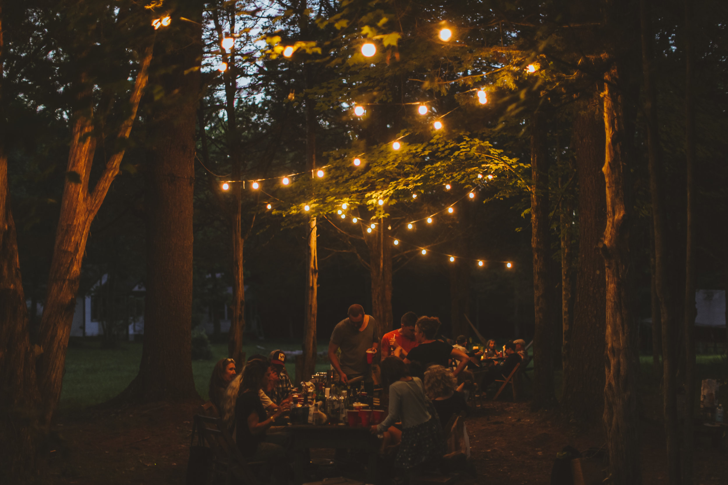 Evening gathering underneath beautiful string lights.   Photo Credit: Peter B Crosby