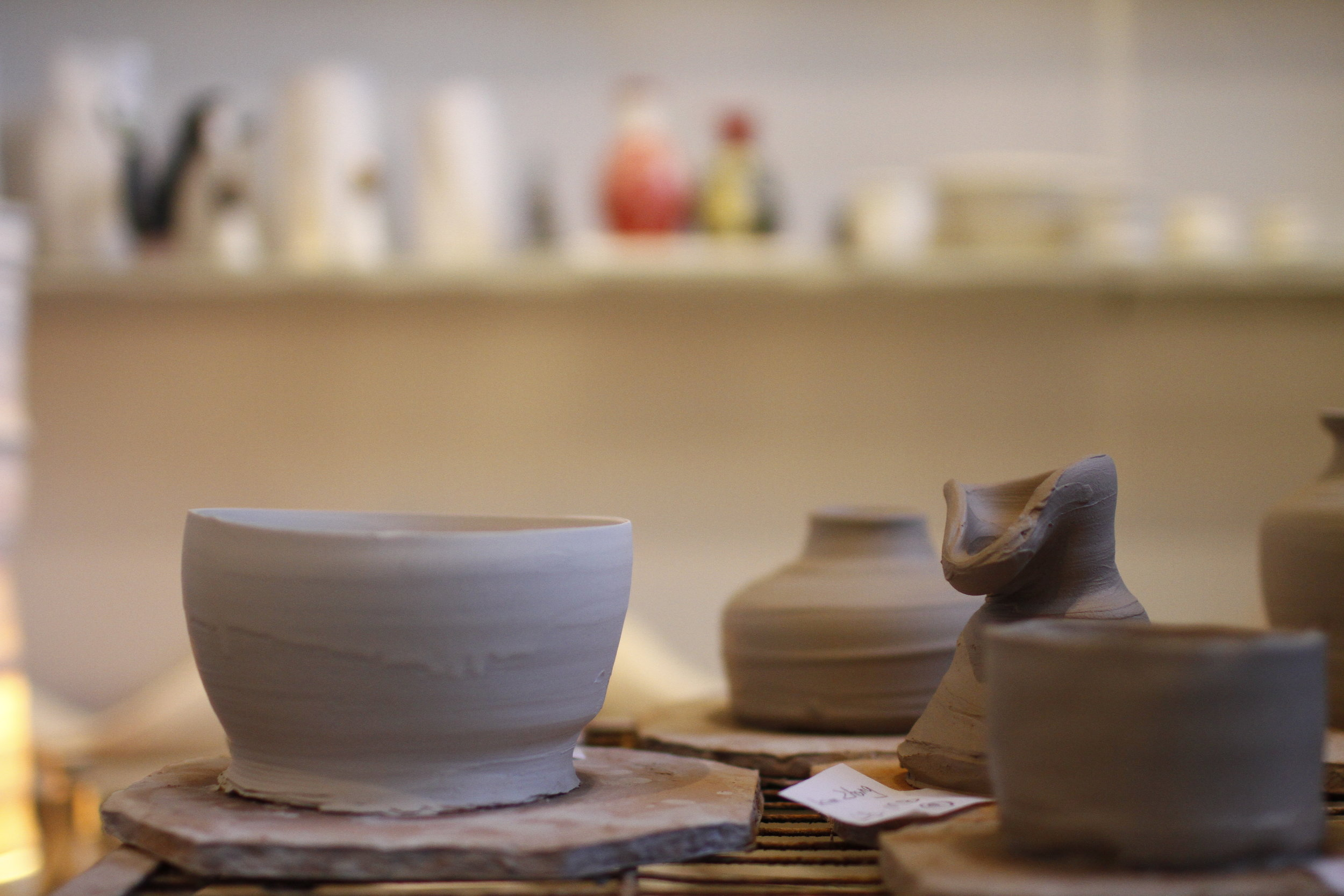 Student ceramic creations drying on the table.