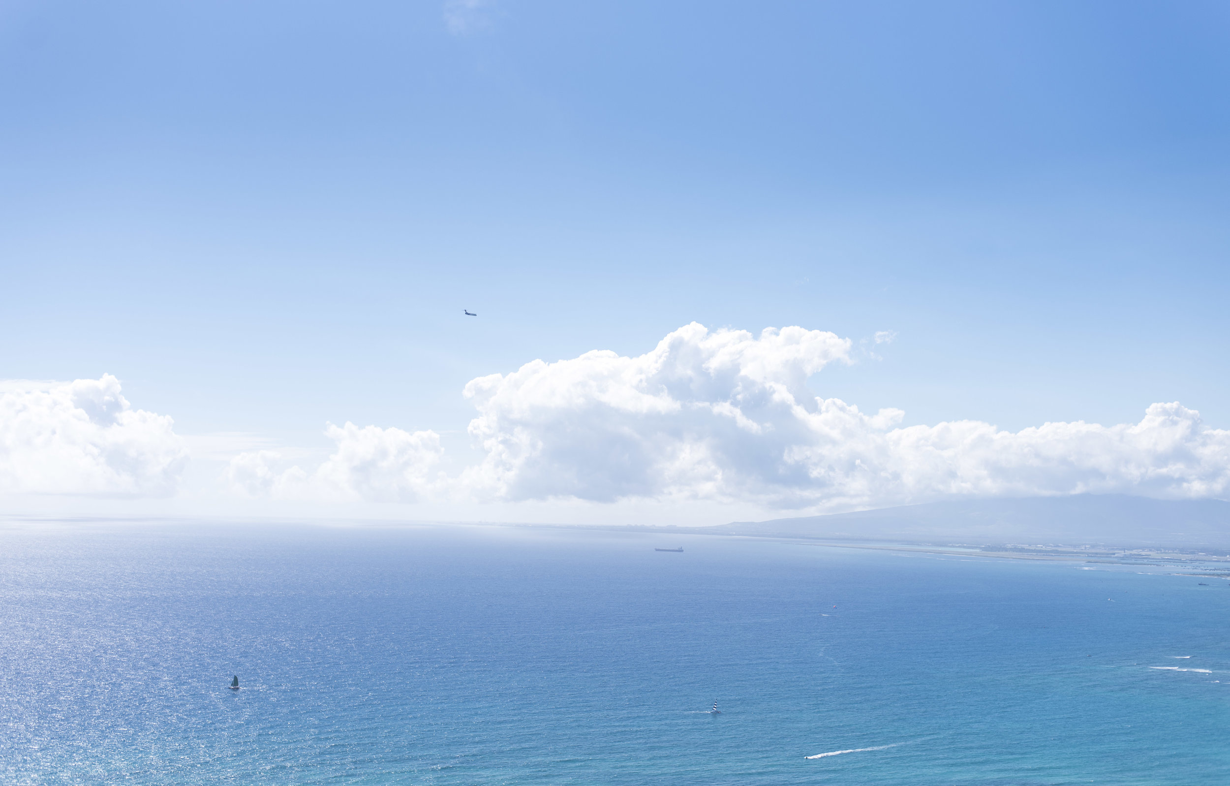 An approaching airplane and tiny sailboats appear as dots on the horizon. Can you spot them all?