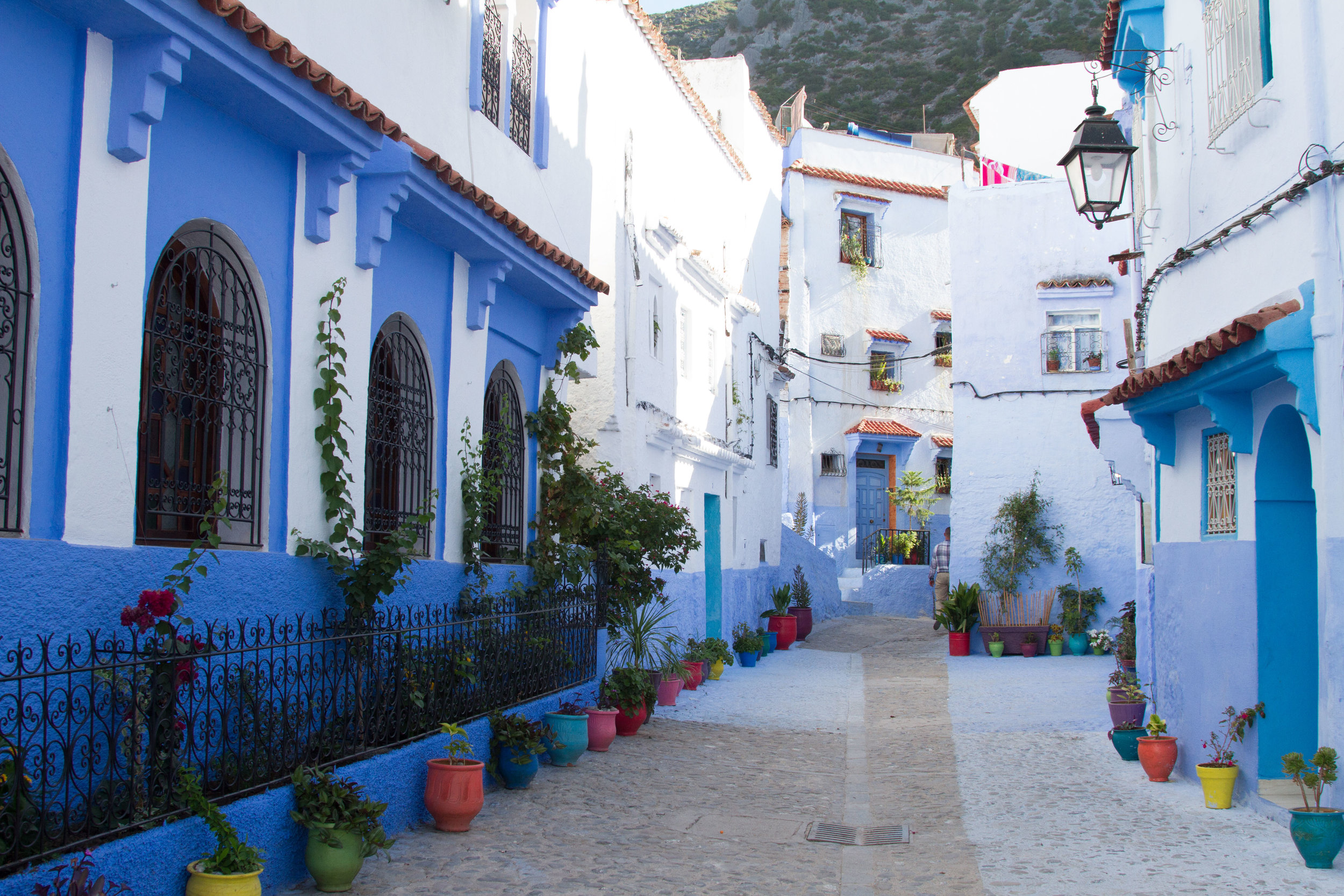 Colourful pots line the street in Chefchaouen