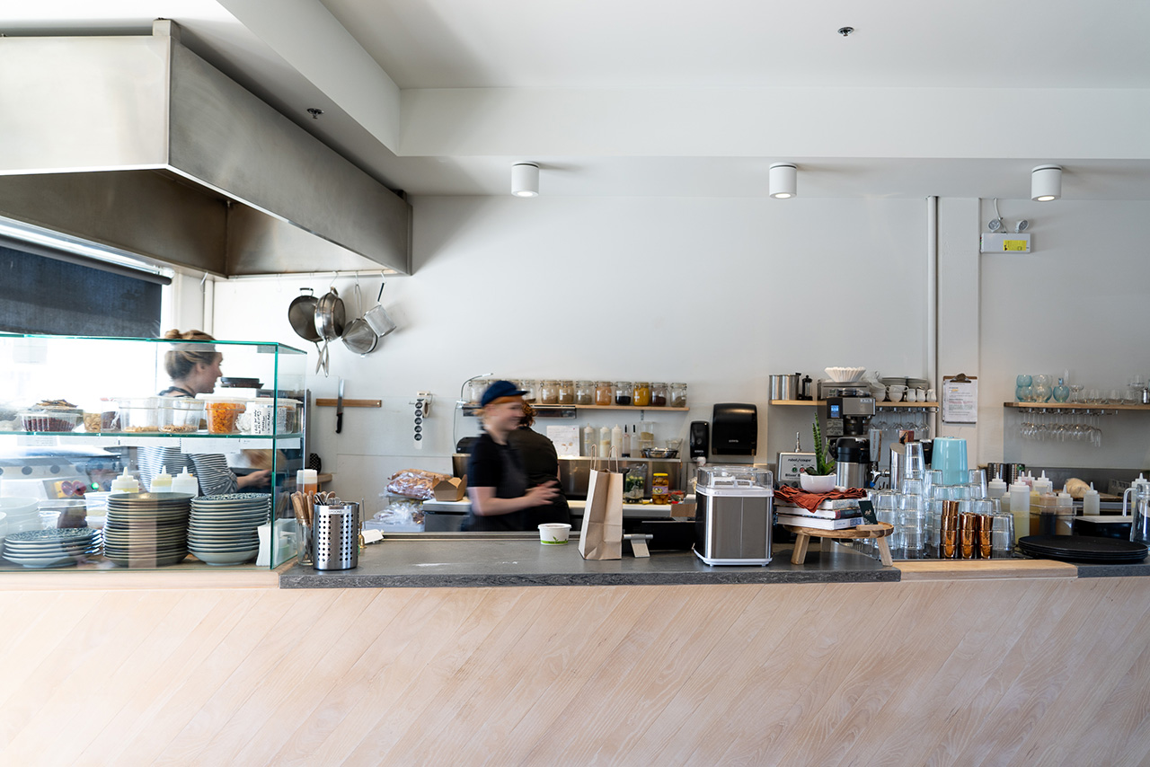 The open kitchen is filled with smiling staff members.