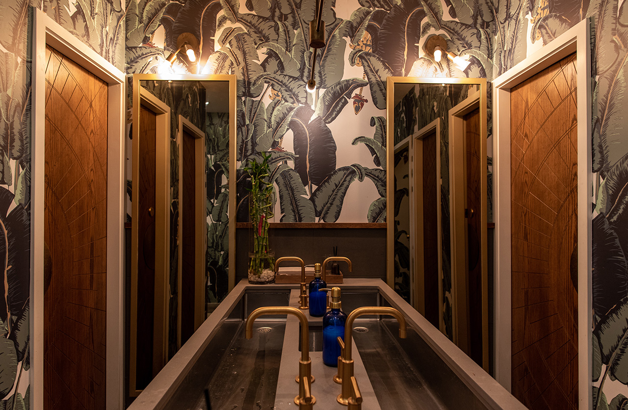 Gender neutral washrooms are intentional, with the wallpaper a reminder of the lush, green jungles of Vietnam.