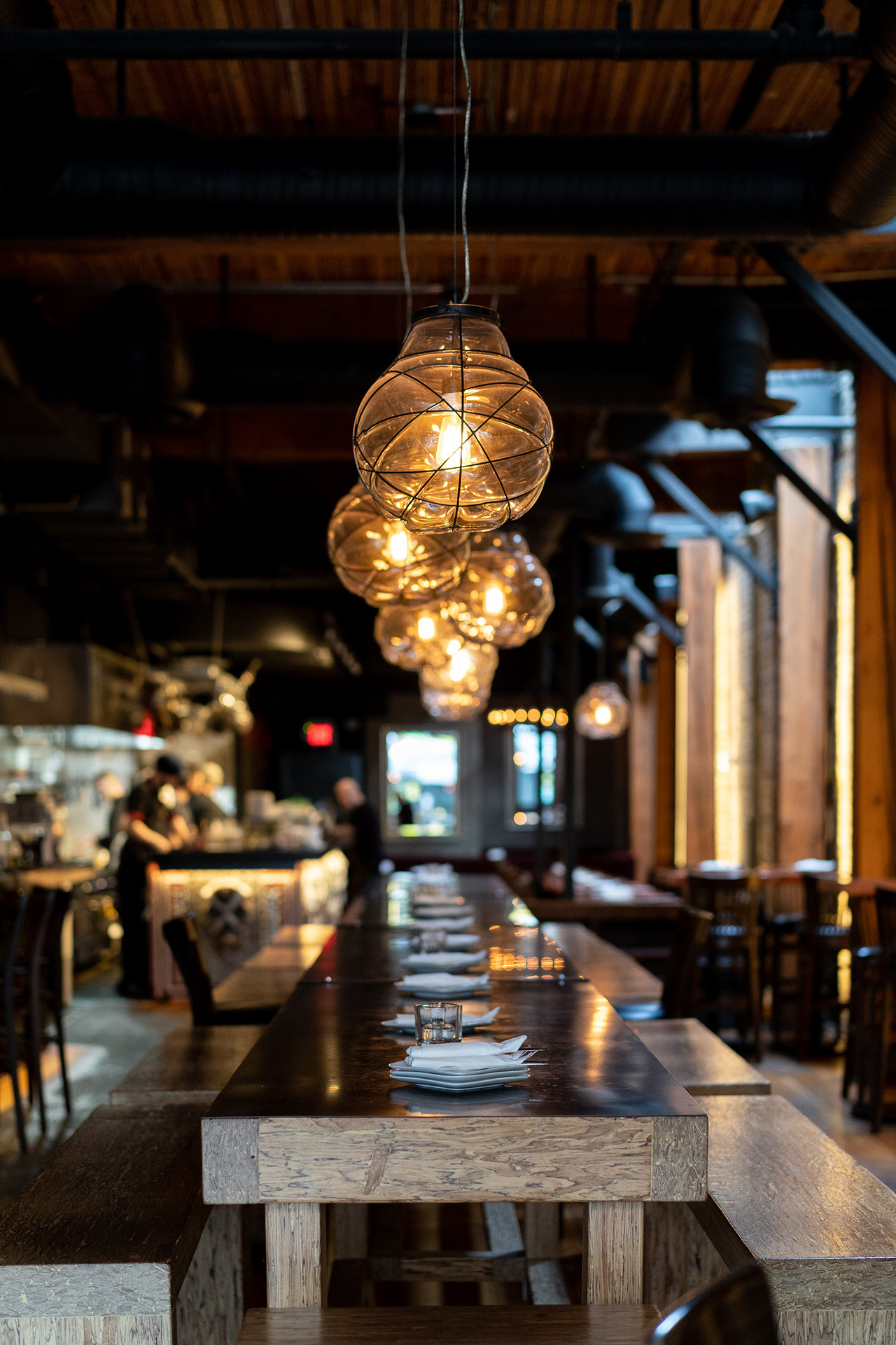 Hand-blown glass chandeliers over the central communal table.