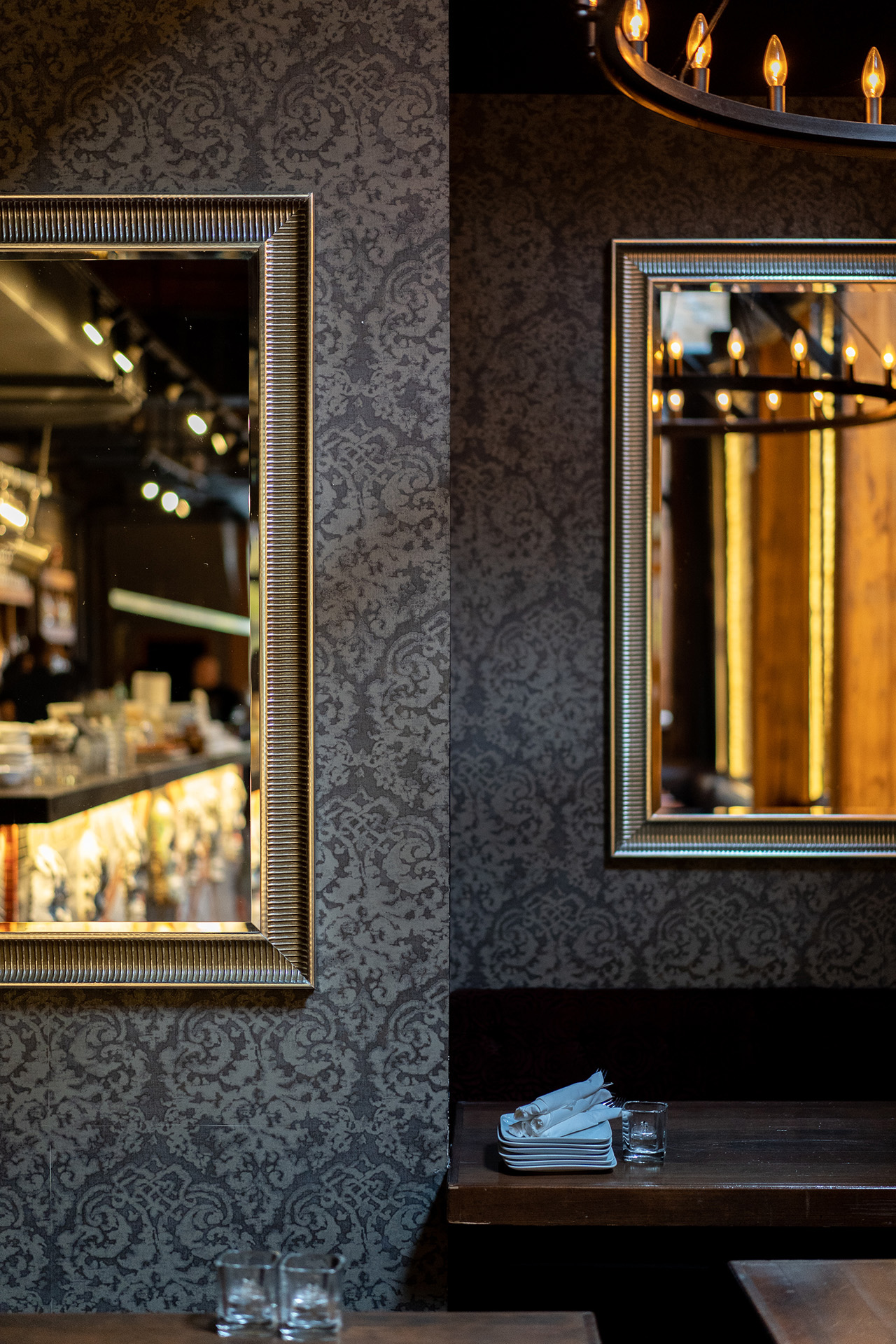 Dark, patterned wallpaper give the dining area at the back of a restaurant a mysterious touch.