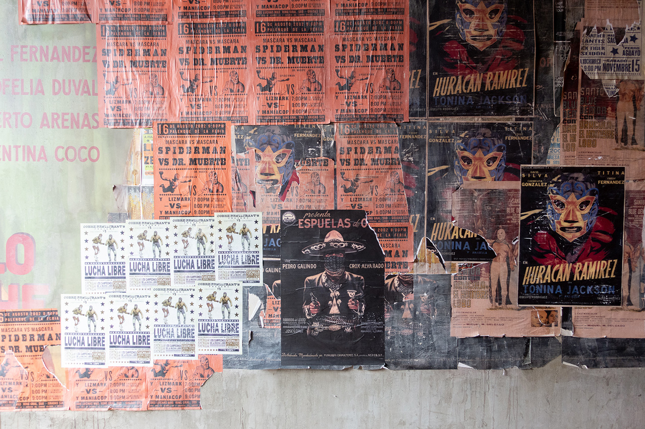 Luchador posters layered atop one another much like you would see them at a Mexican soccer stadium.