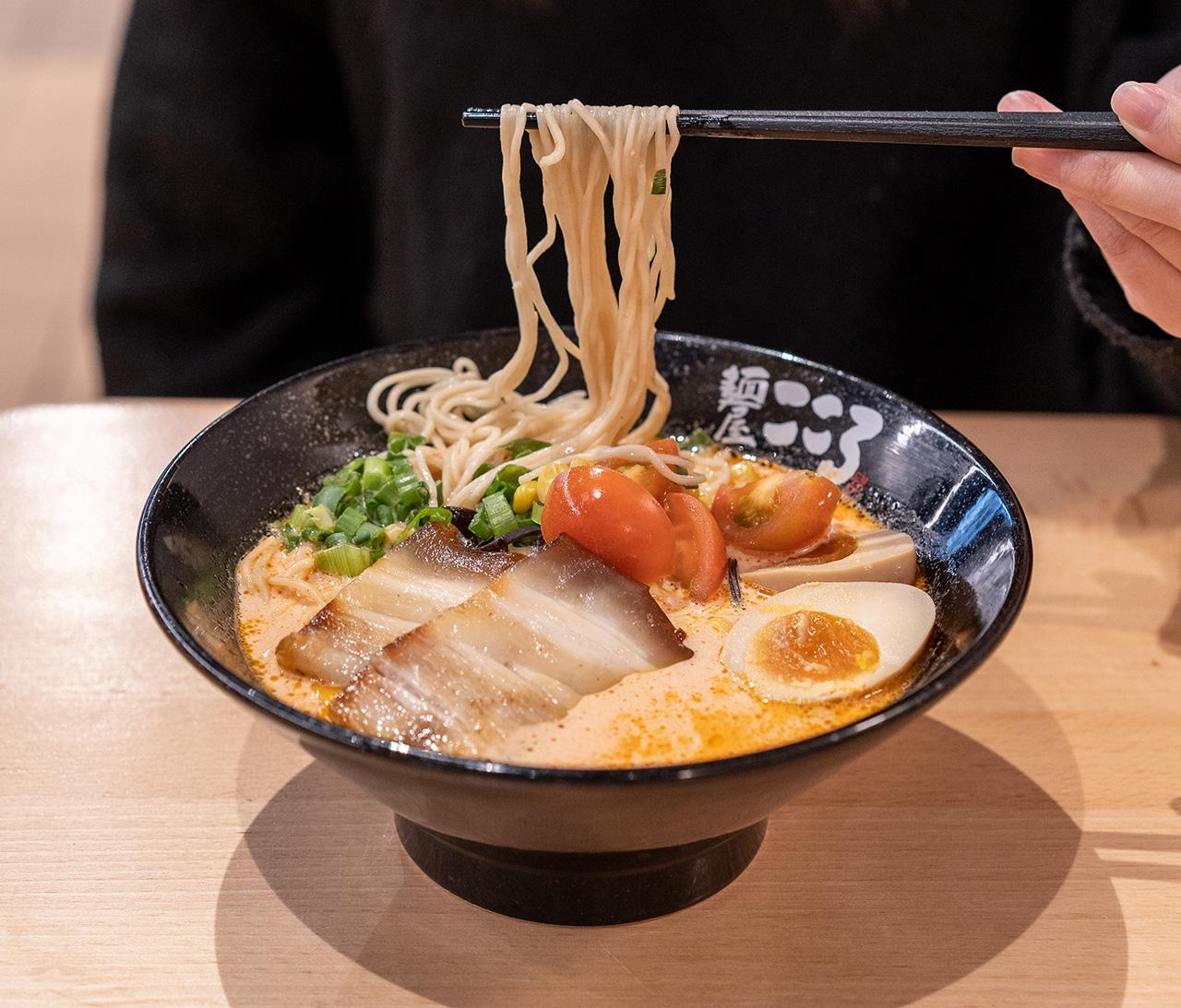 Thin ramen noodles soak up the creamy tomato pork broth.
