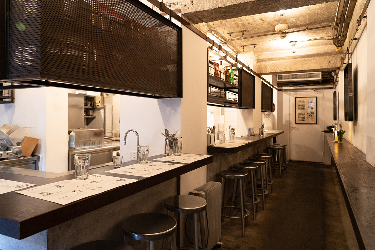 Cozy, intimate dining area designed with patrons seated around the bar and others sipping their drinks standing along the wall.