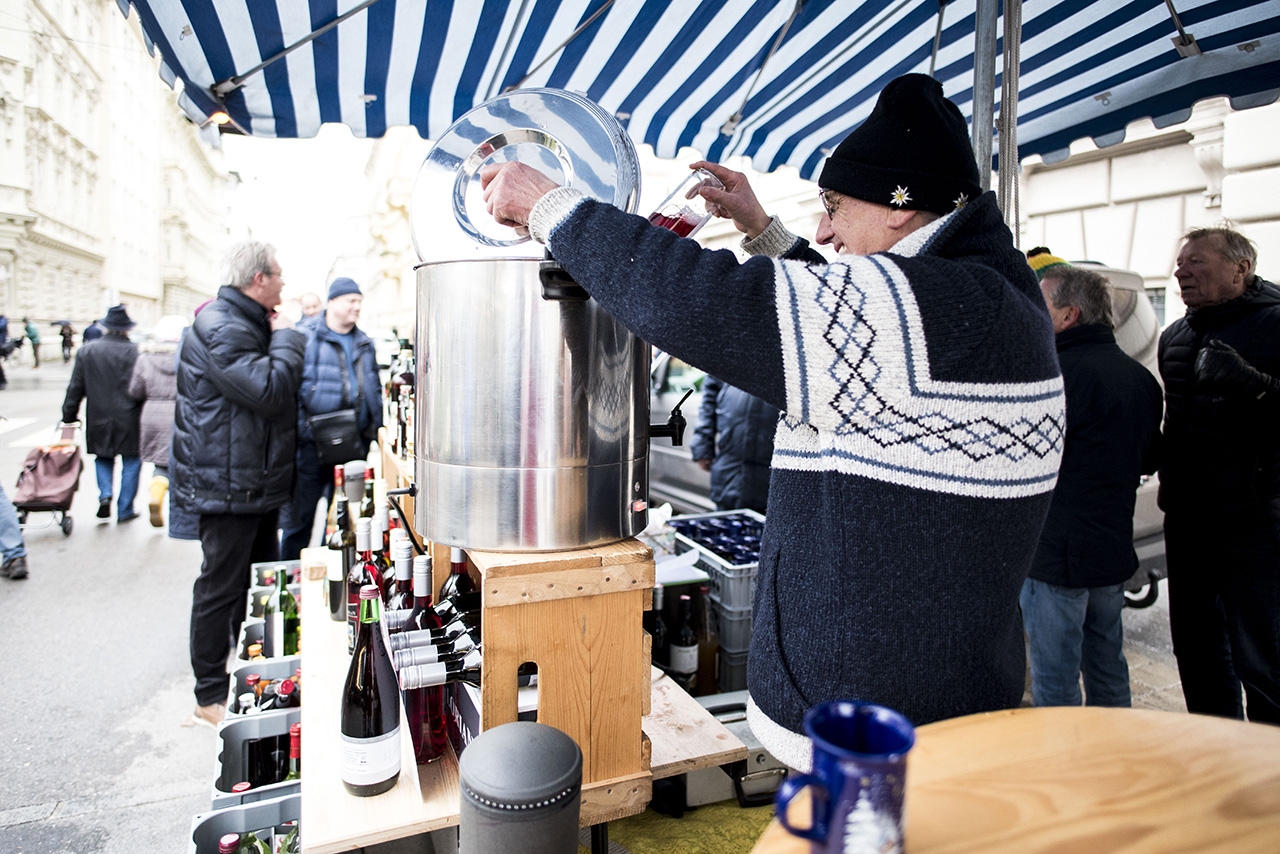 Cheery wine vendor served up numerous cups of mulled wine to passerby.