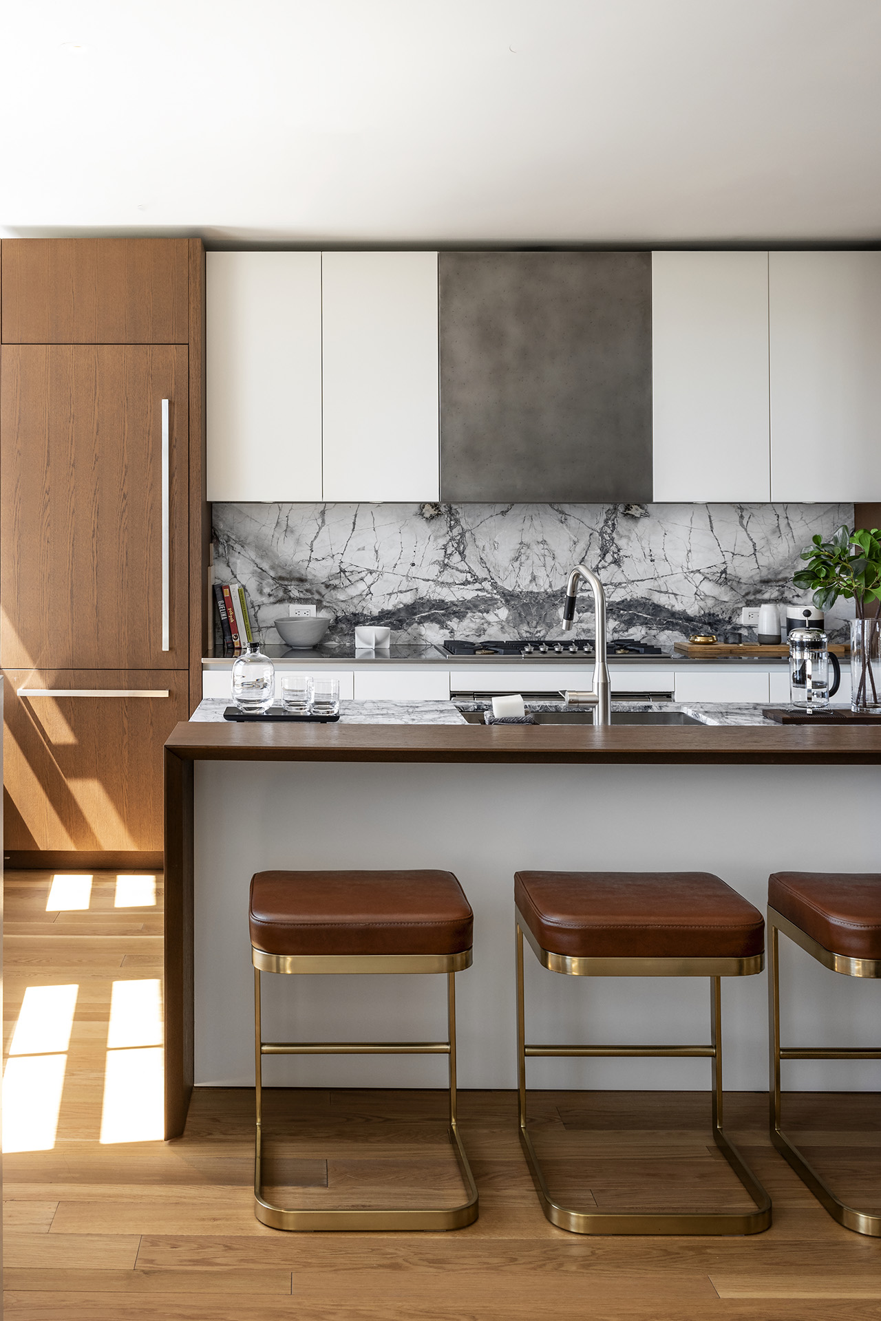 A rich mix of materials from stone, marble and wood is featured in the kitchen, accented by bronze highlights and plush, chocolate leather bar stools. Photo by Gianni Franchellucci.