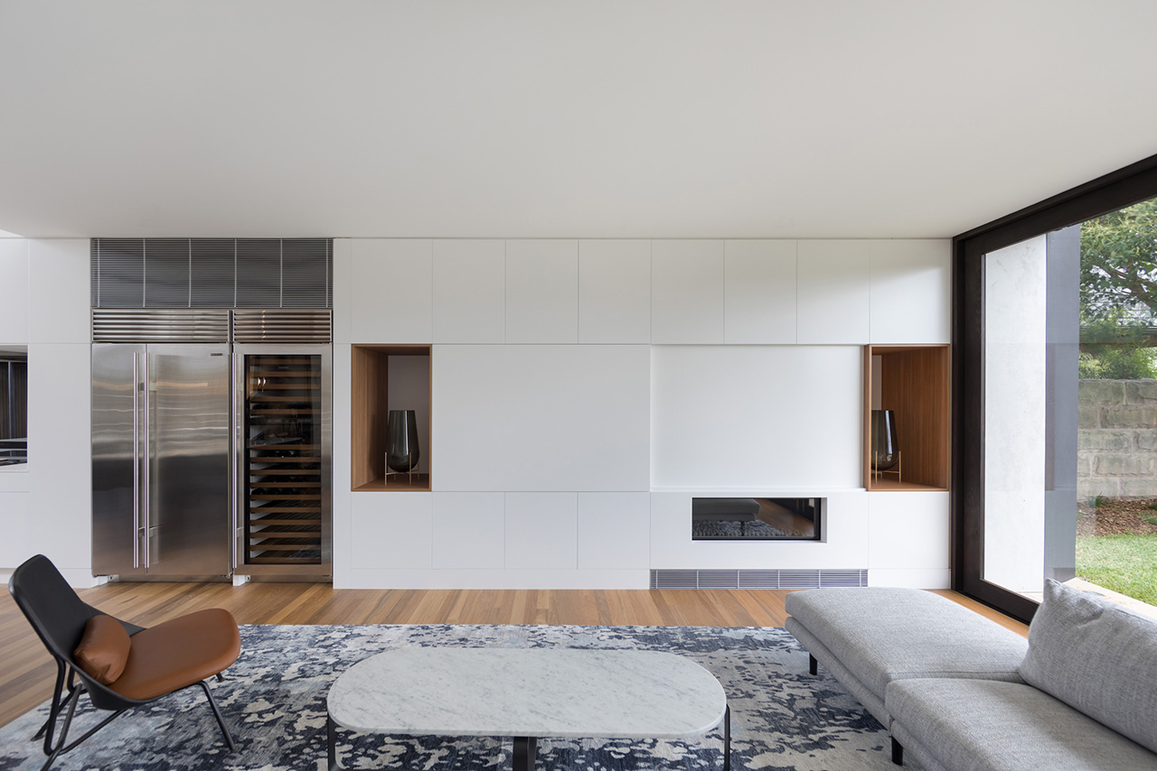 Living square with an integrated floor-to-ceiling storage system concealing the entertainment system when one desires a disconnection from electronic devices.