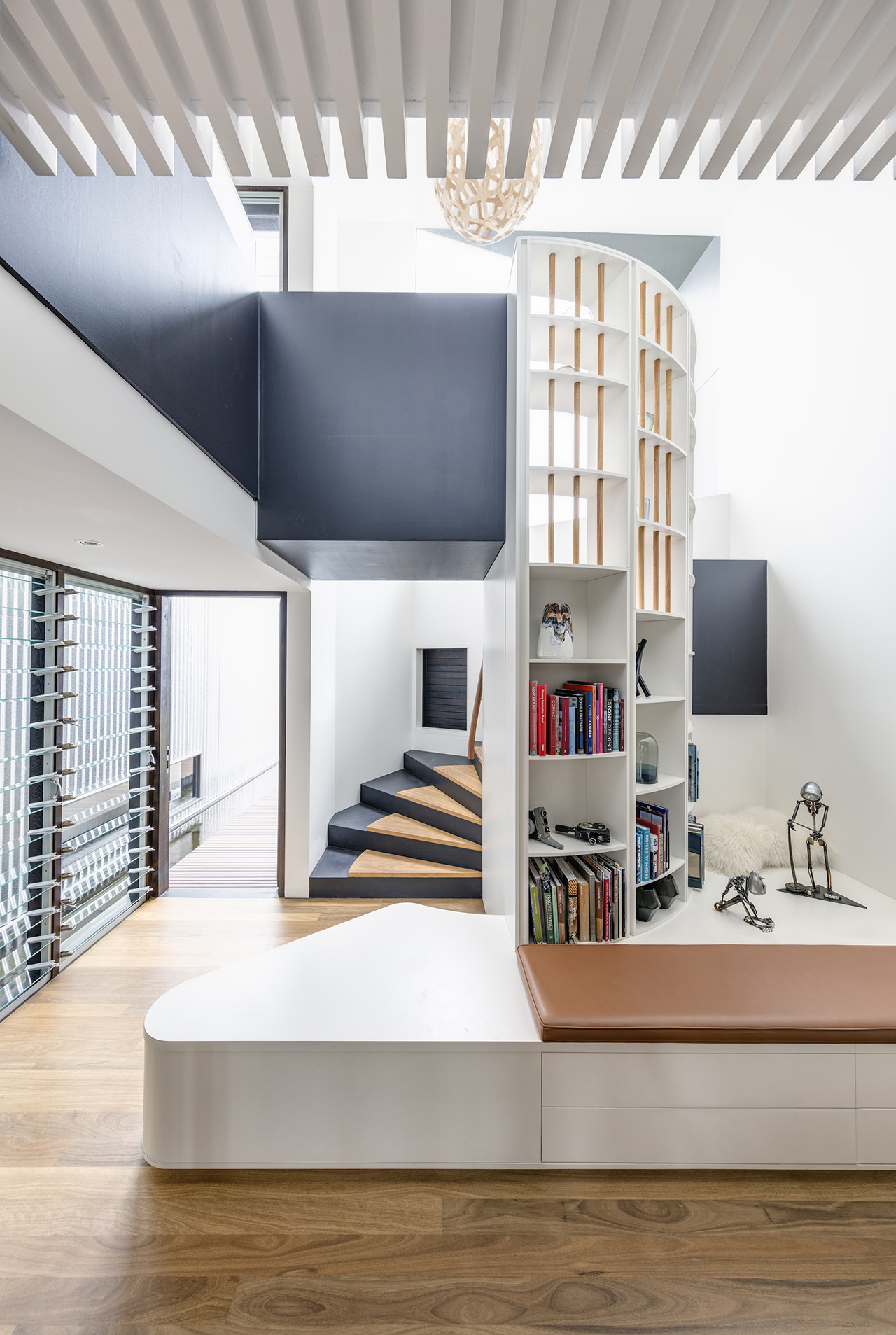 Spiral staircase leading to the second floor serving a second purpose to create a reading nook.
