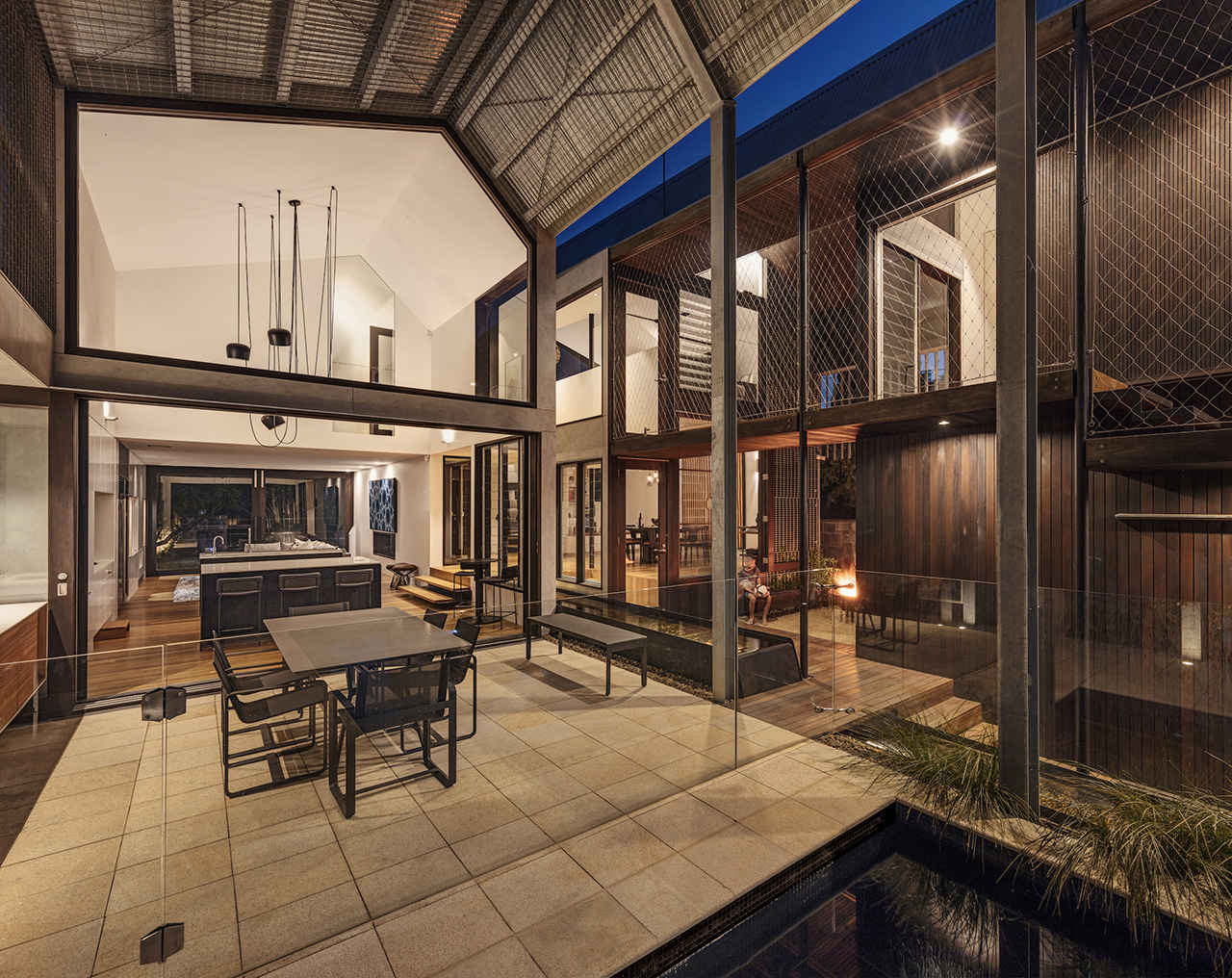 Outdoor dining area with a view of the outdoor pool and also a passive view of the upstairs bedrooms seamlessly integrated with the walkway.