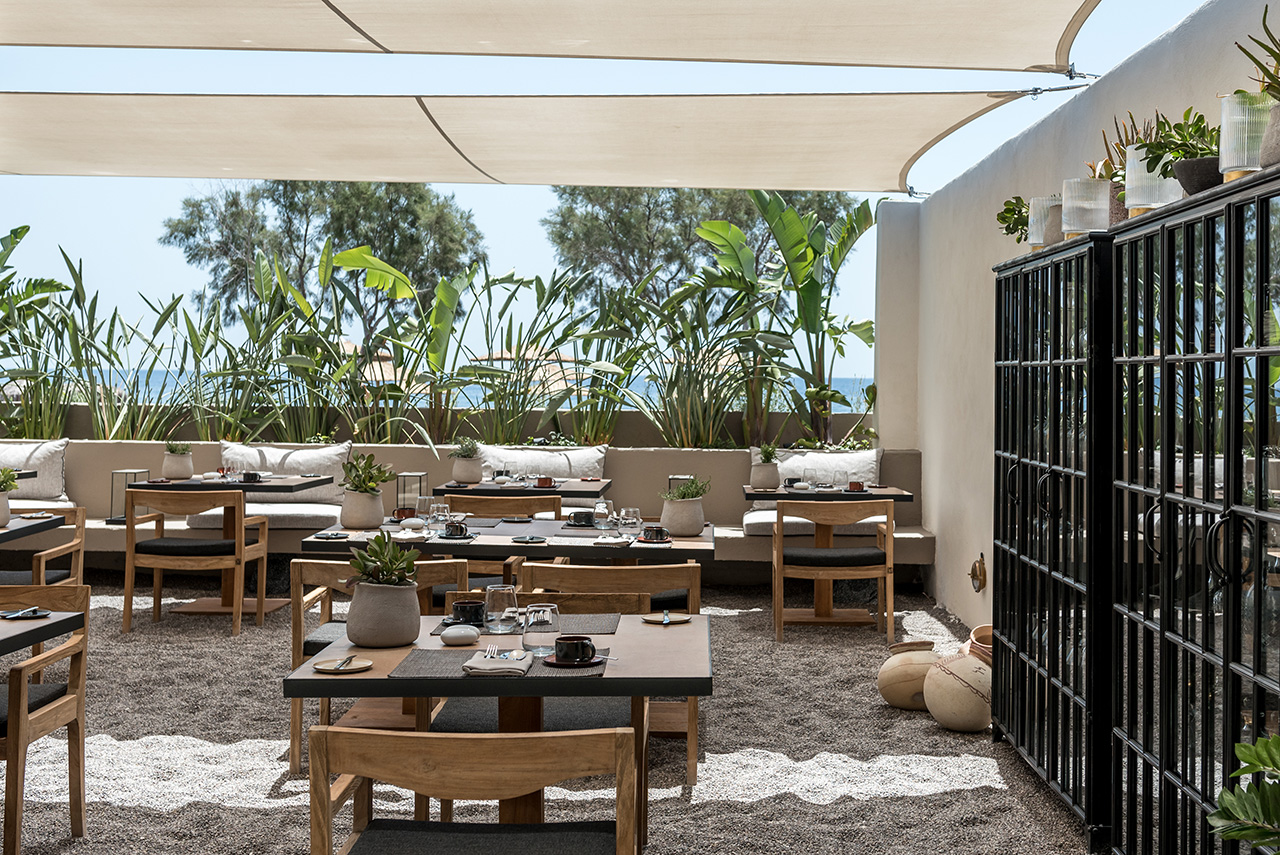 Enjoy breakfast or lunch at the hotel's outdoor dining area with dark, volcanic sand under your feet.