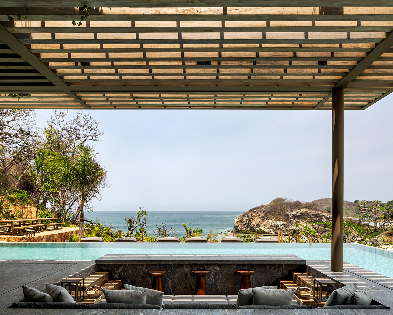A sunken social space looking out to the infinity pool and beyond to the sea.