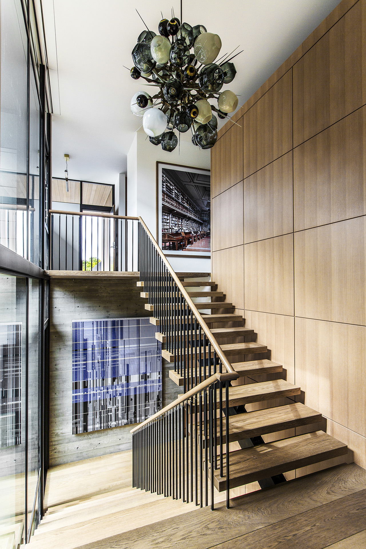 A Boom Boom Burst chandelier by Lindsey Adelman hangs above the staircase. A photograph by Candida Höfer and a painting by Liu Wei are displayed on the walls.
