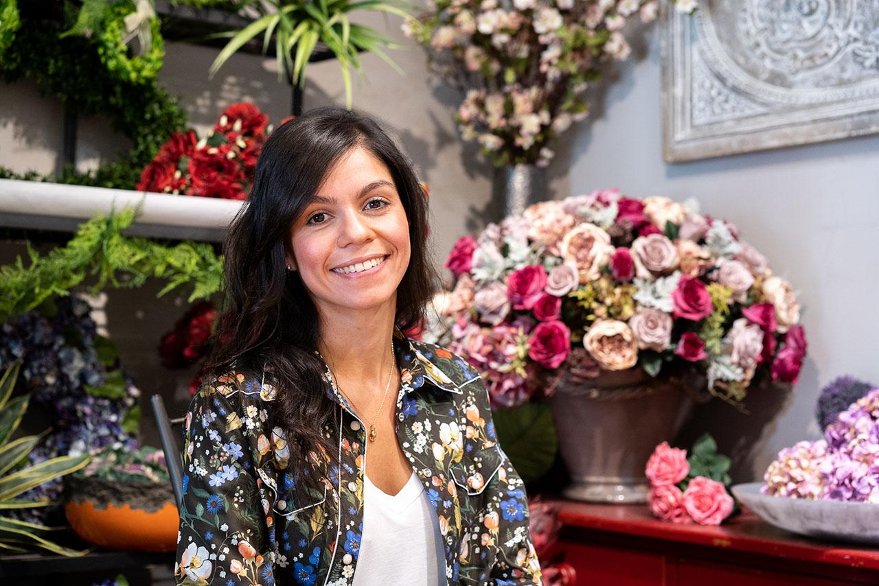 Helen in front of their beautiful silk floral arrangements.