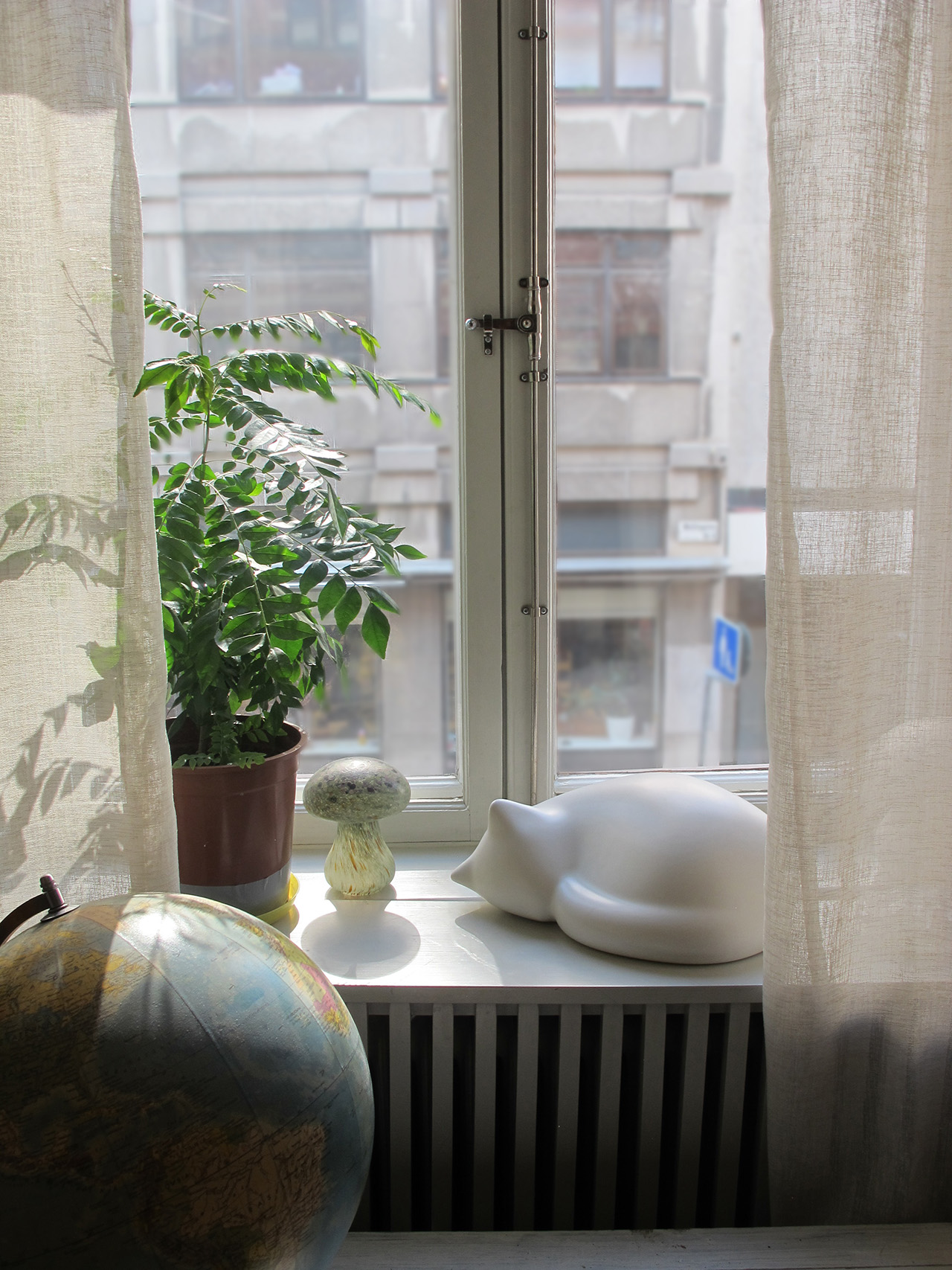 By the window quietly observing the city's streets.