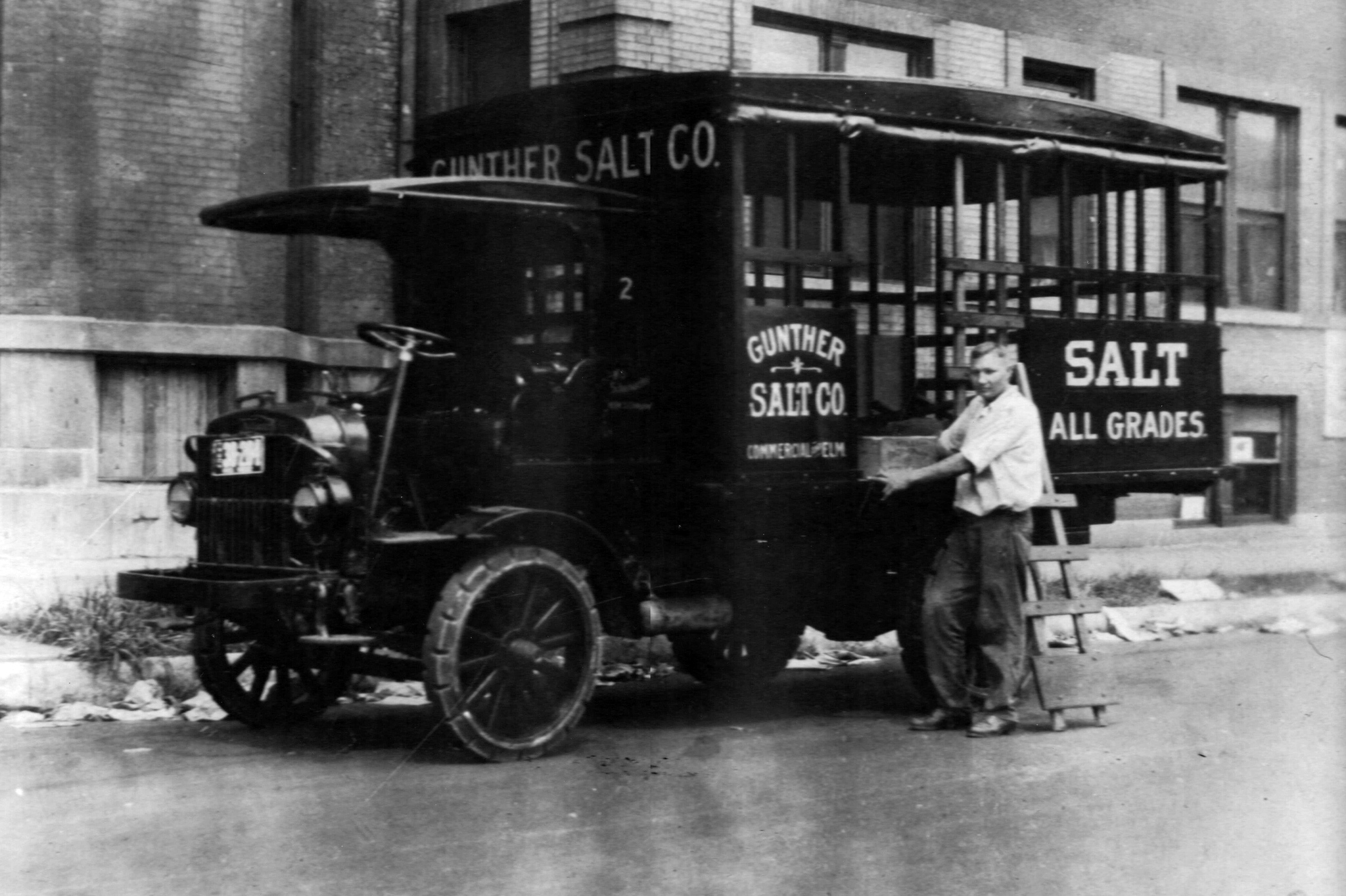 An employee of Gunther Salt Company is either loading or unloading the Gunther Salt Company truck to make his salt delivery. This photo has a date of August 15, 1922.