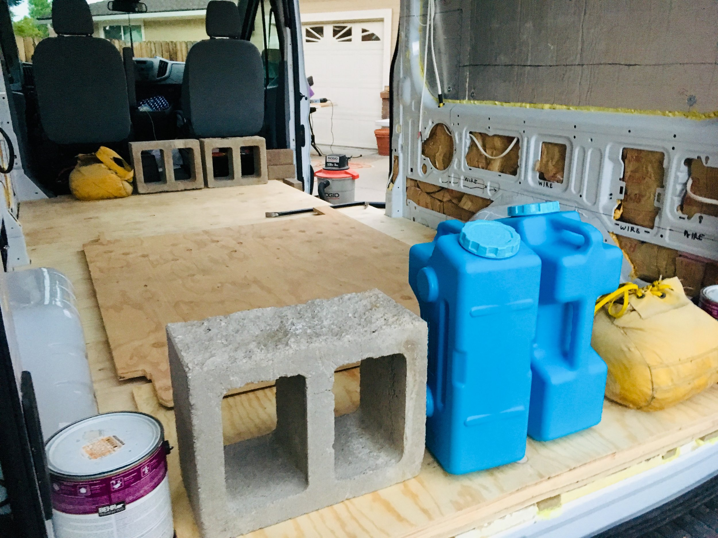 We weighed down the subfloor with everything we could find…. including a couple of the water jugs that we're going to use for my sink system.