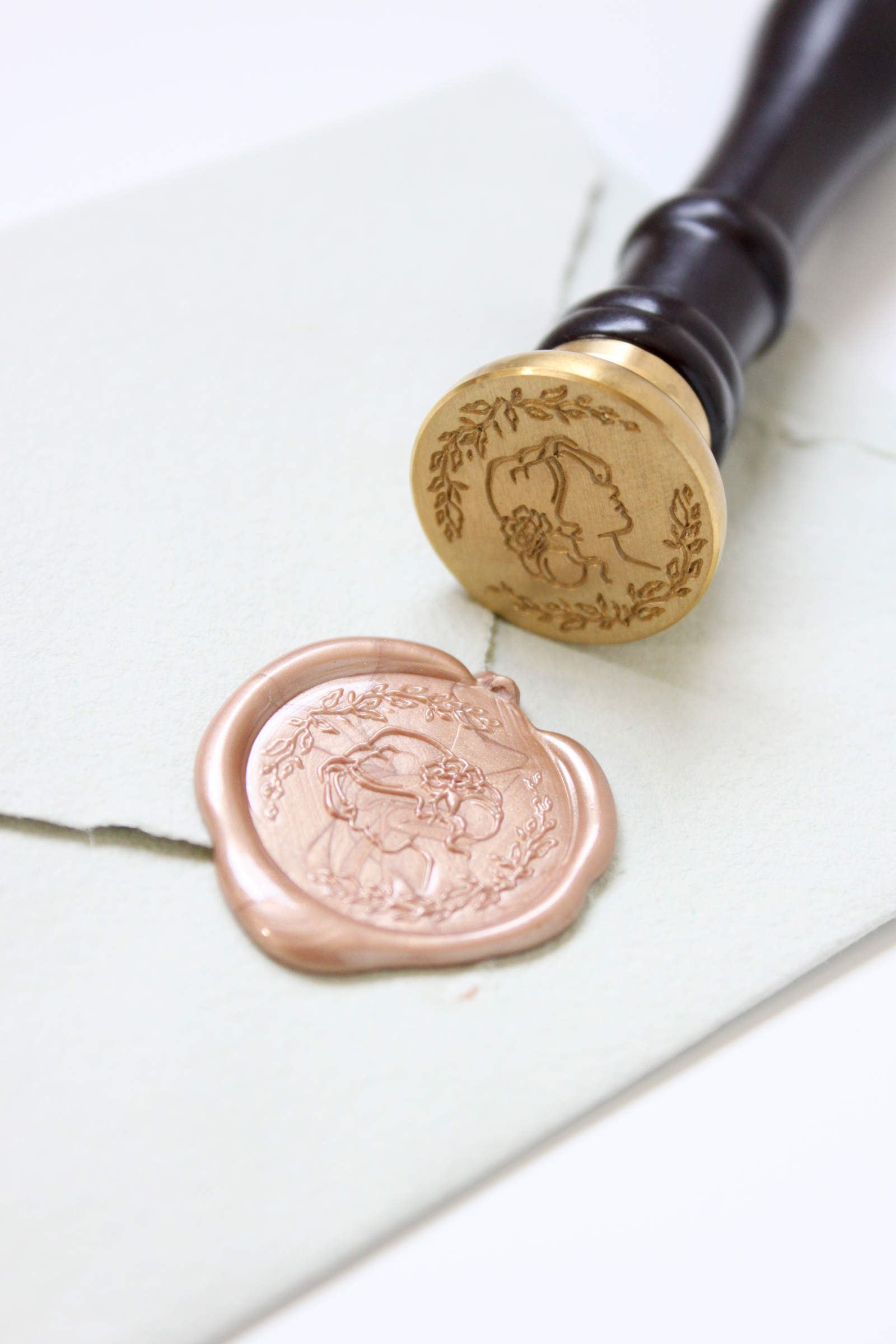 """How to use wax seals.  Stamp wax seals like a pro with these tips from professional fine art stationer, Katrina Crouch! Rose gold wax featuring the """"Blushed Bride"""" seal exclusively at Artisaire.com 