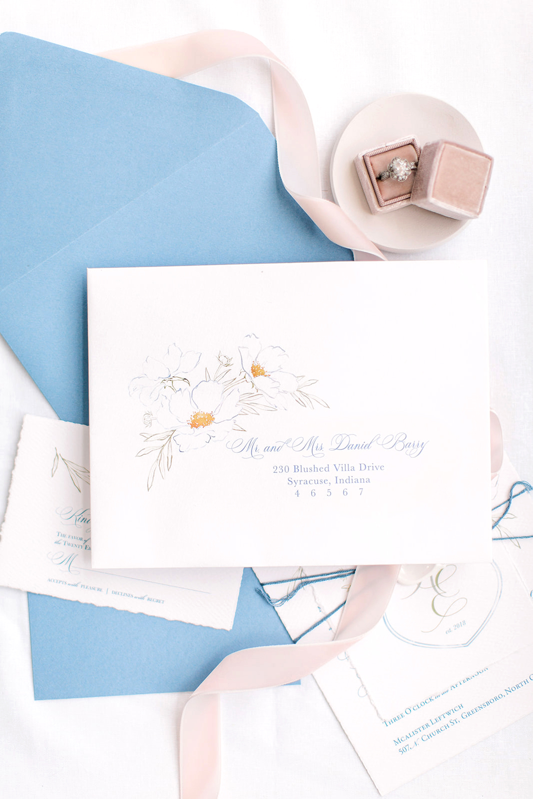 Beautiful calligraphy envelopes featuring watercolor artwork on the envelope for a fine art wedding.  Handmade paper envelopes and artwork by Katrina of Blushed Design, Wedding INvitaitons and Fine Art Portraits