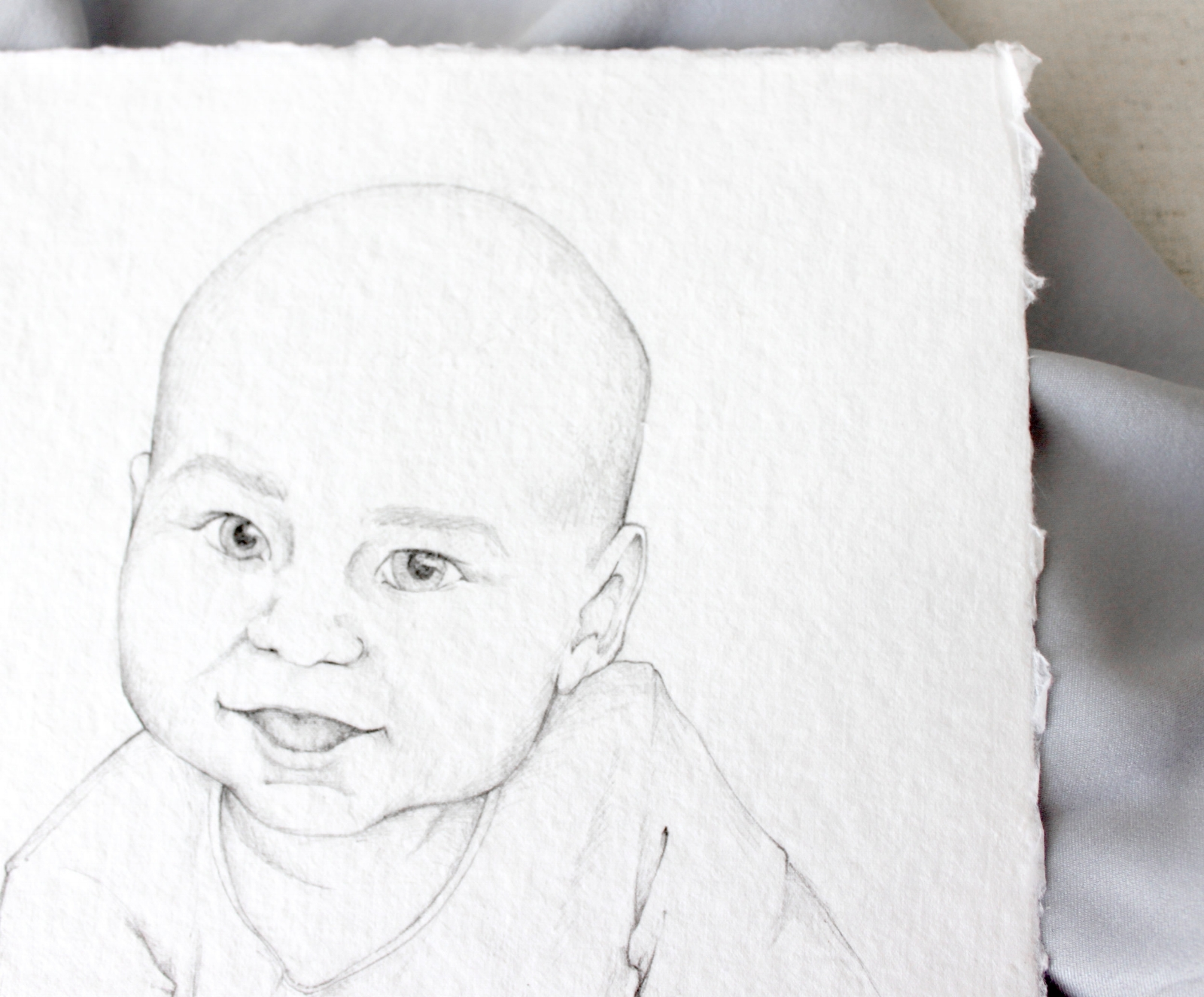 Custom portrait of baby in pencil on handmade paper.  Illustration by Katrina of Blushed Design, paper by Fabulous Fancy Pants. #fineartportrait #pencildrawing #customportrait