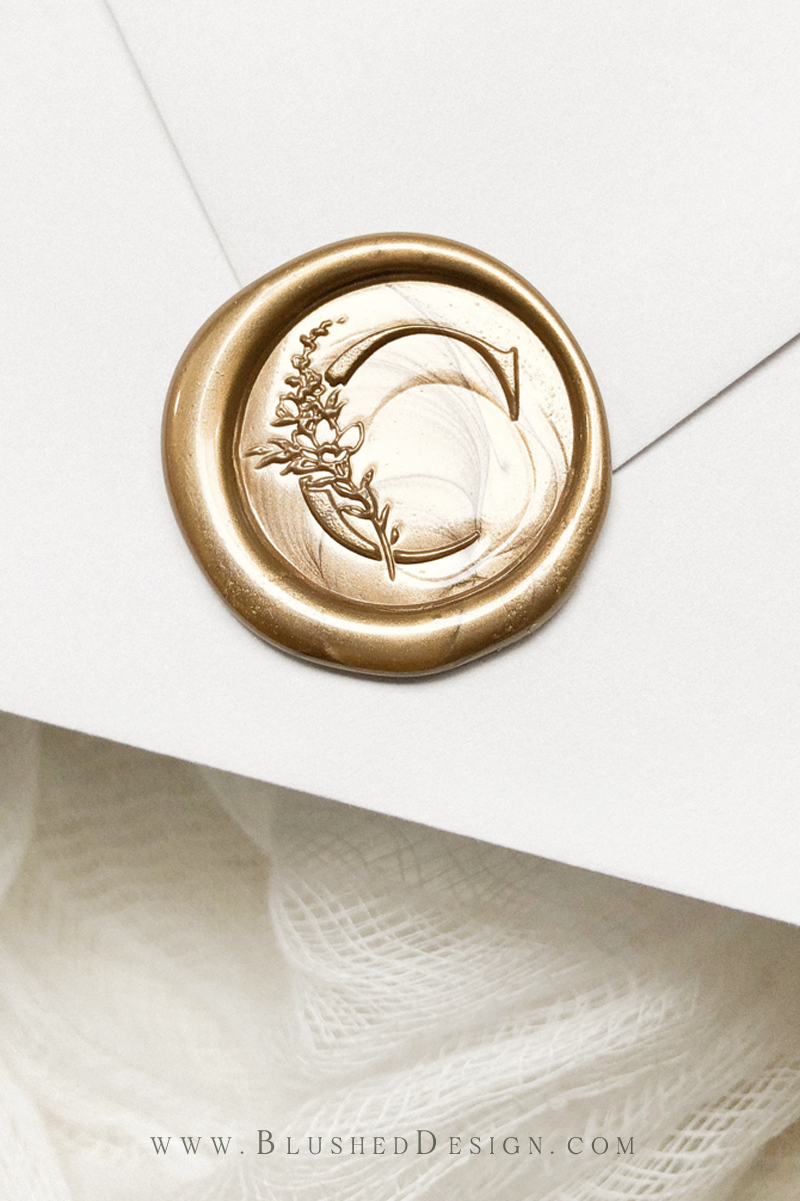 A beautiful monogram wax seal that is sure to turn heads! Use the botanical initial wax seal stamp from Blushed Design to make a jawdropping impression on your wedding guests, before they even come to your ceremony! Shown here in antique gold #waxseal #weddingwaxseal #monogramwaxseal #personalizedwaxseal #goldwaxseal #antiquewaxseal